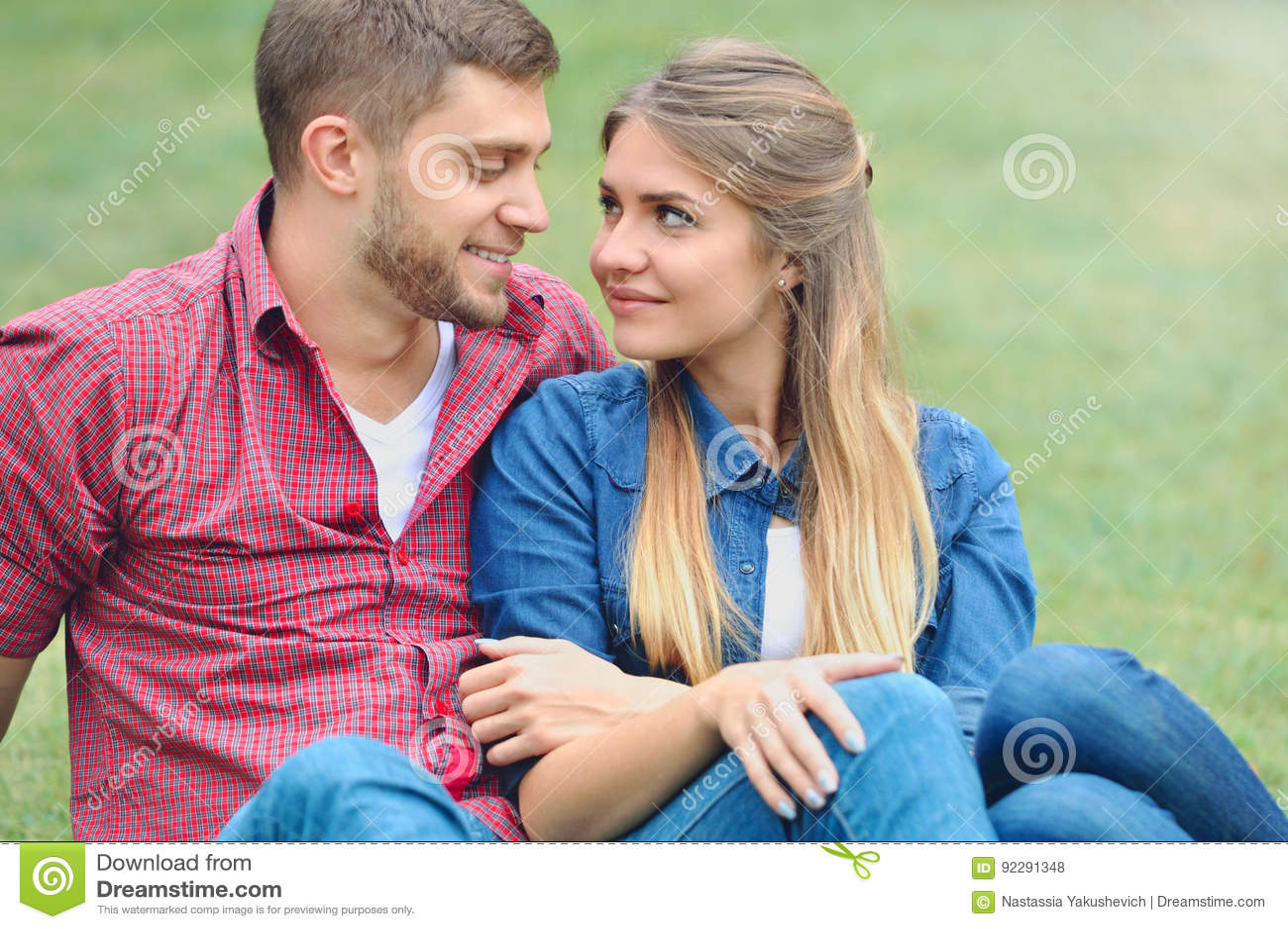 Couples romantiques se reposant sur l herbe et le regard dans l un l autre yeux du ` s