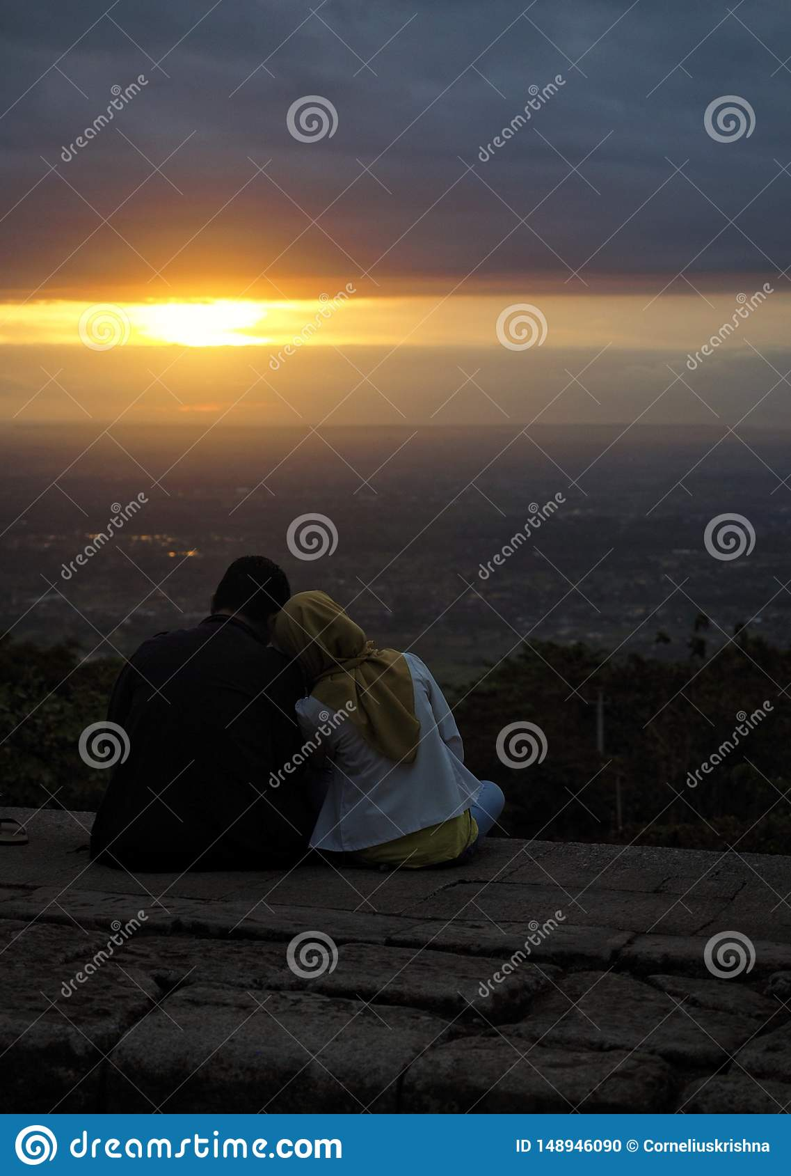 Couples sitting on a rock while looking to sunset. Taken in Ijo temple, yogyakarta, Indonesia