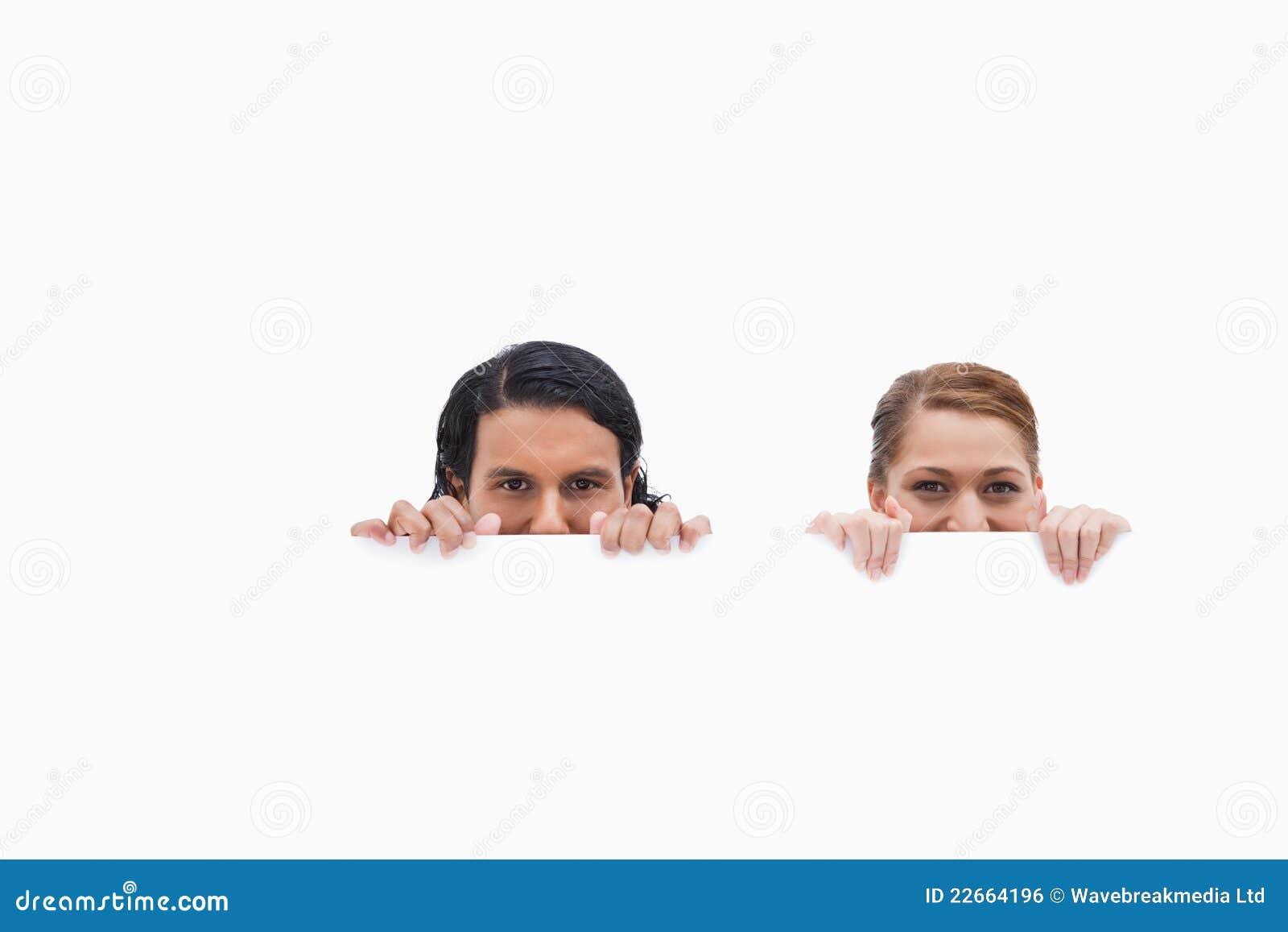 Couples Sneaky regardant au-dessus du mur blanc