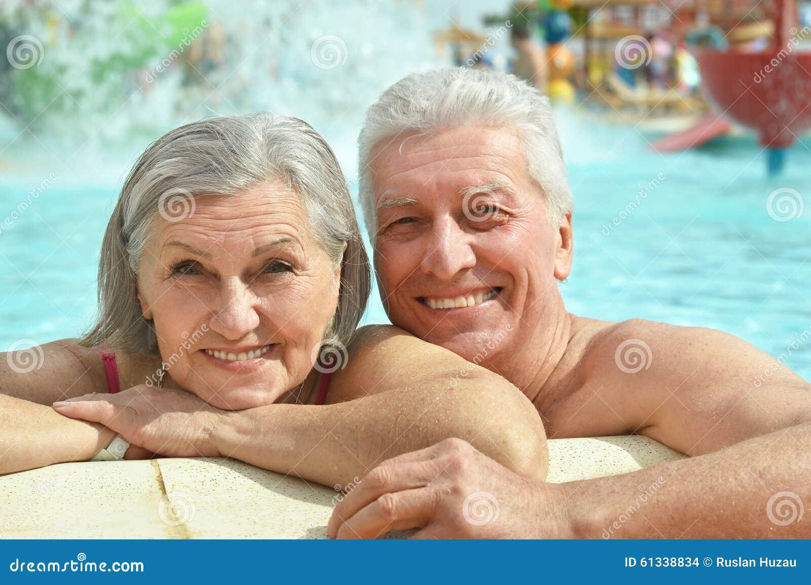 Couples supérieurs détendant à la piscine