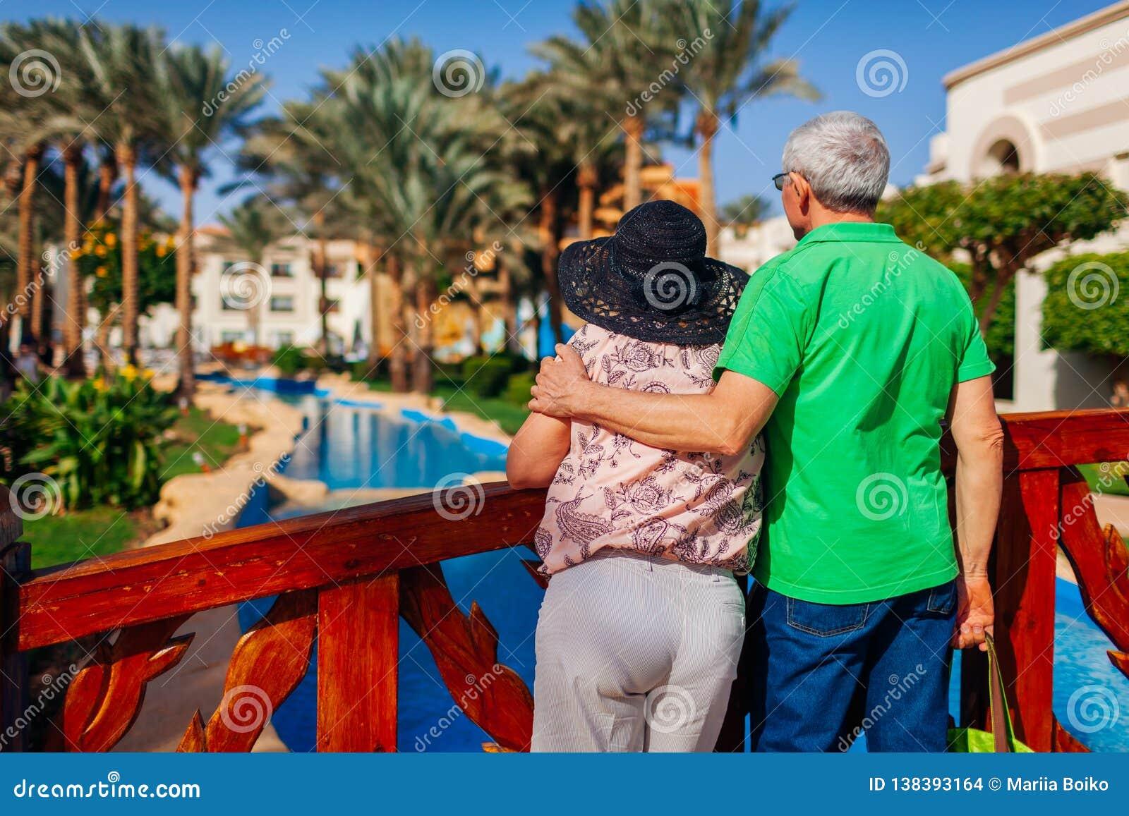 Couples supérieurs détendant par la piscine sur le territoire d hôtel Les gens appréciant des vacances Jour du `s de Valentine