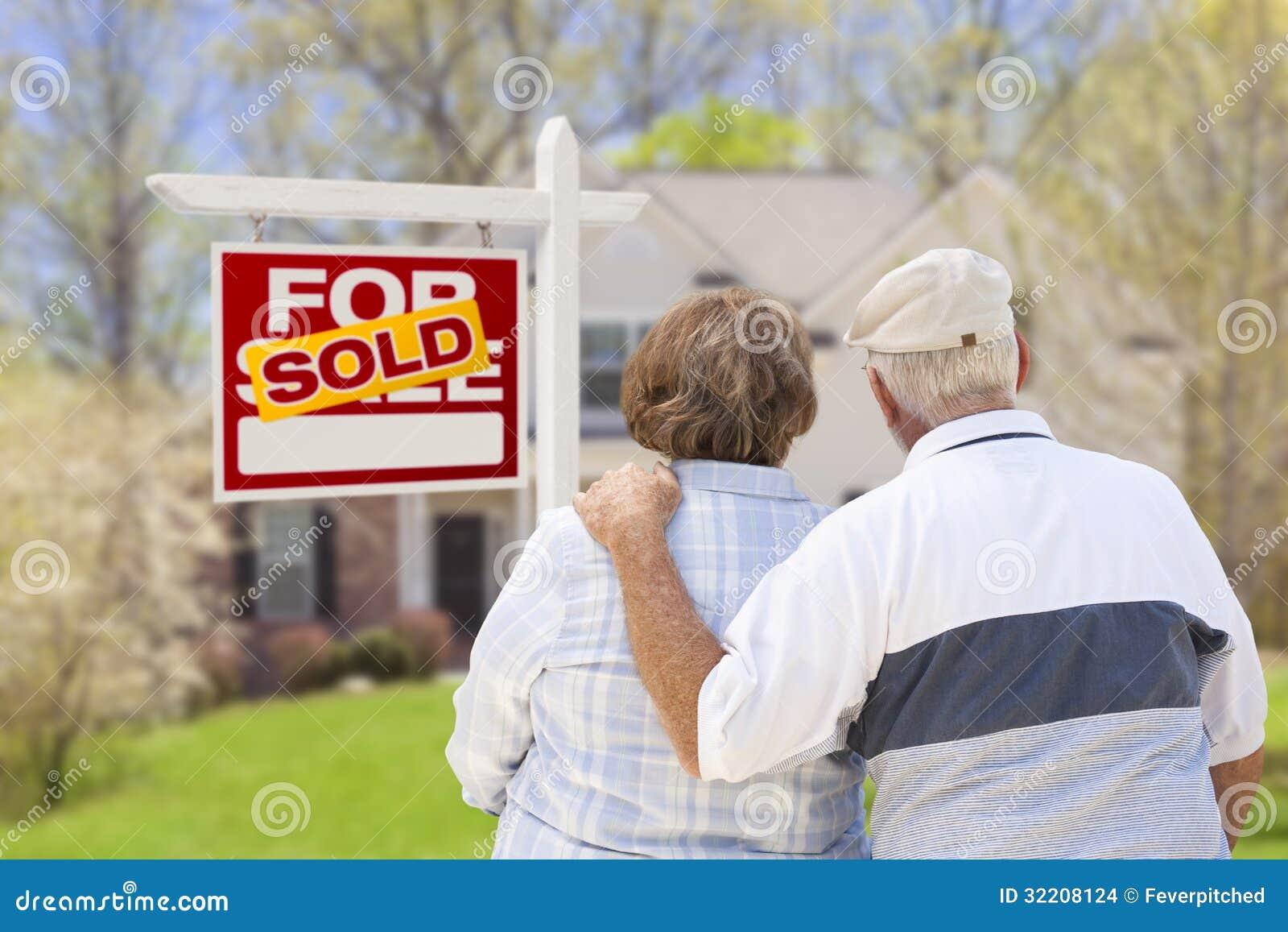Couples supérieurs devant le signe et la Chambre vendus de Real Estate