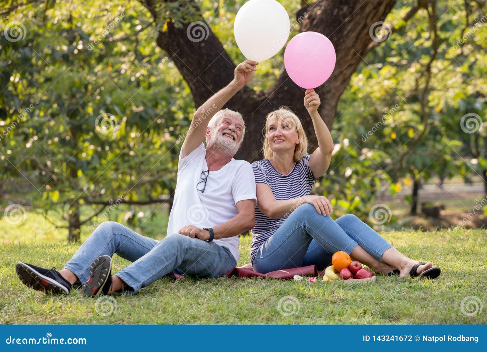 Couples supérieurs heureux détendant en parc jouant des ballons ensemble personnes âgées s asseyant sur l herbe en parc d été Rep
