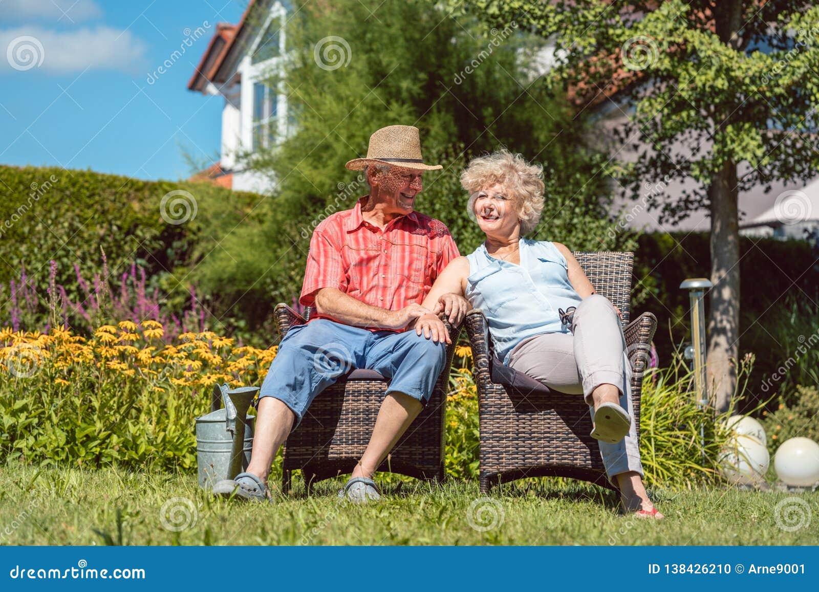 Couples supérieurs heureux dans l amour détendant ensemble dans le jardin en été