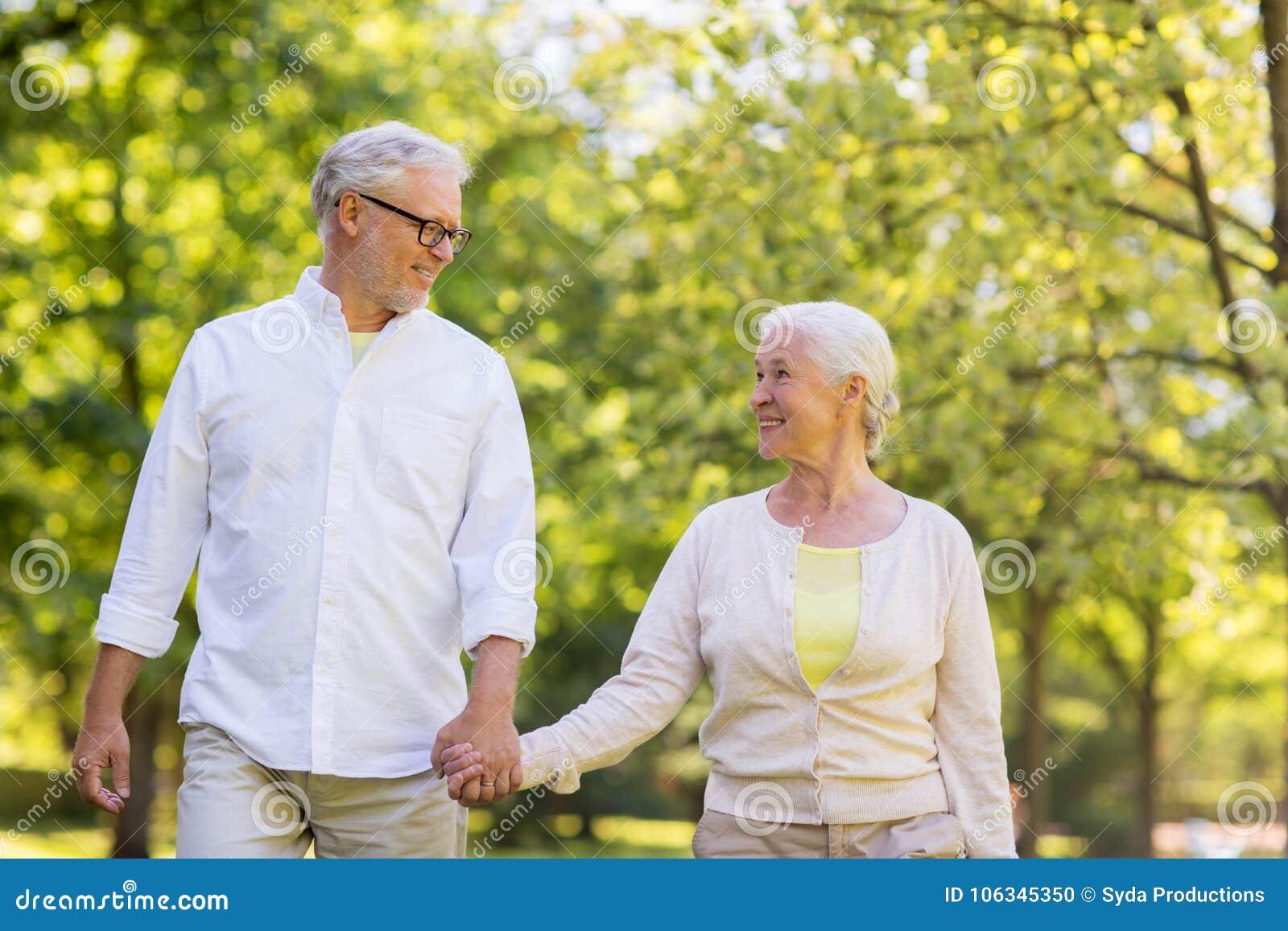 Couples supérieurs heureux marchant au parc d été