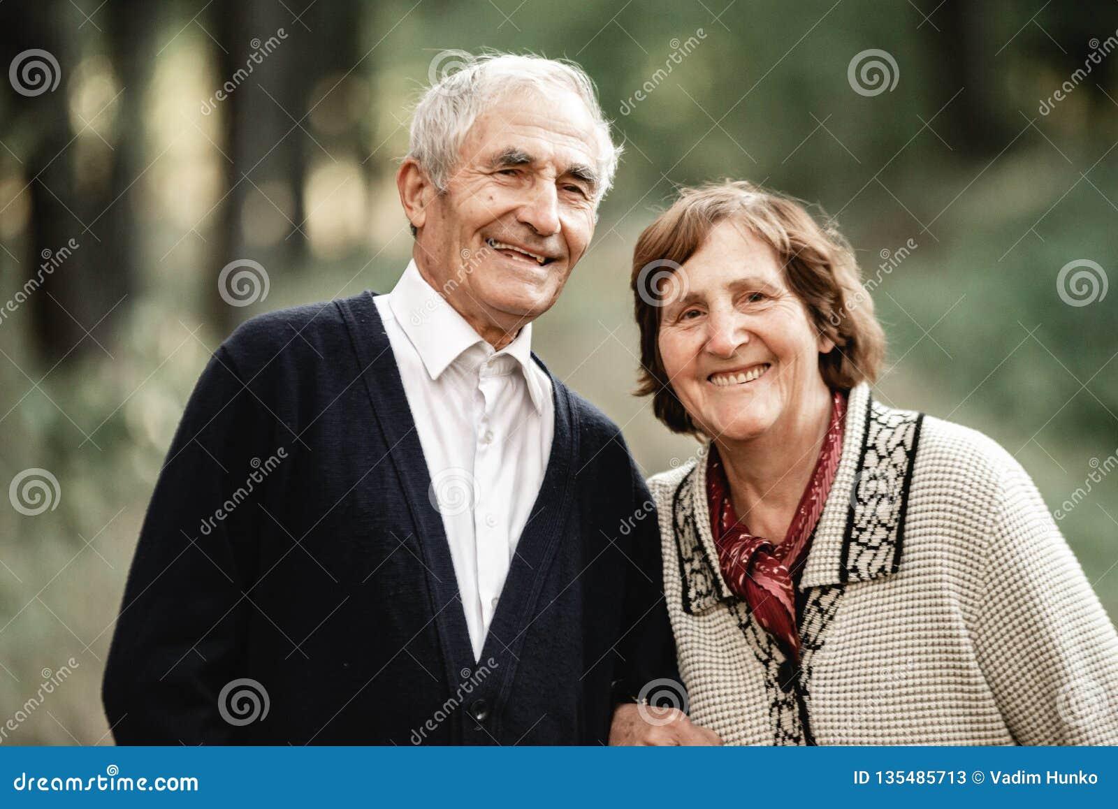 Couples supérieurs heureux marchant en parc