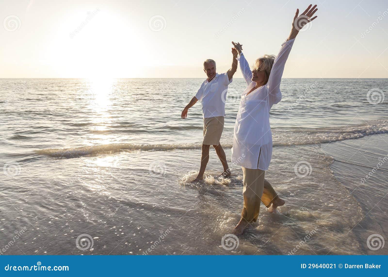 Couples supérieurs heureux retenant la plage de lever de soleil de coucher du soleil de mains