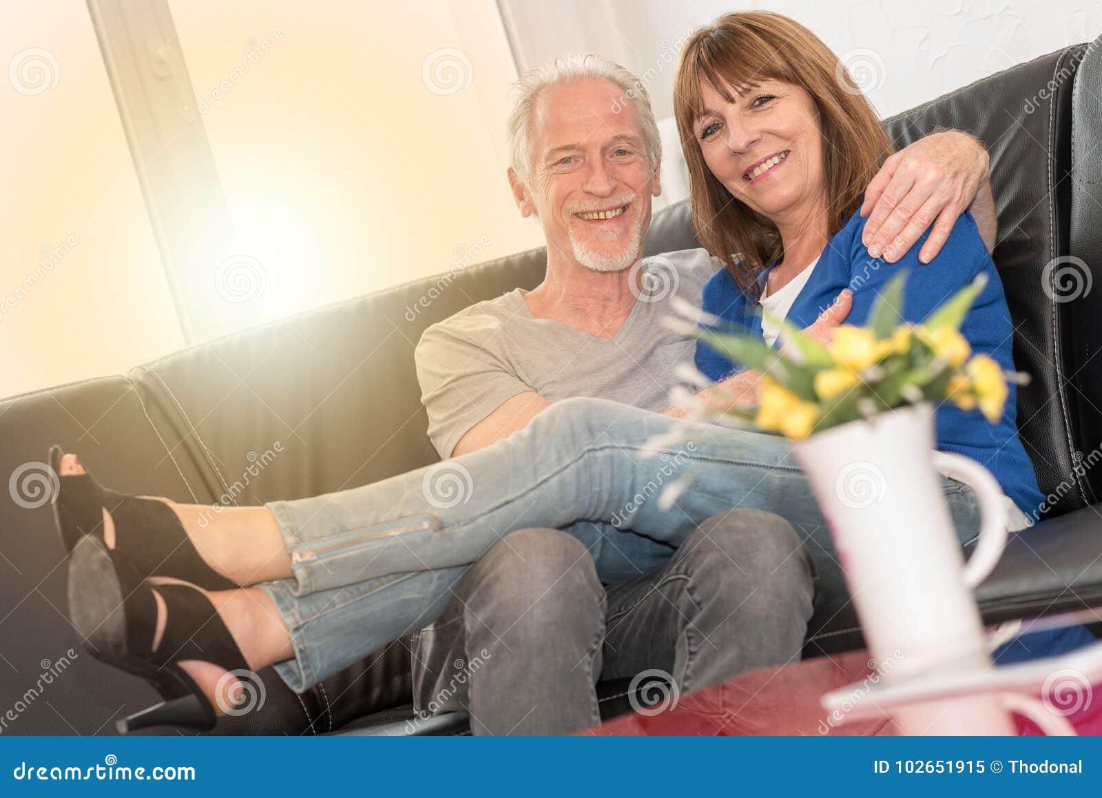Couples supérieurs heureux se reposant sur le sofa et s embrassant, effet de la lumière