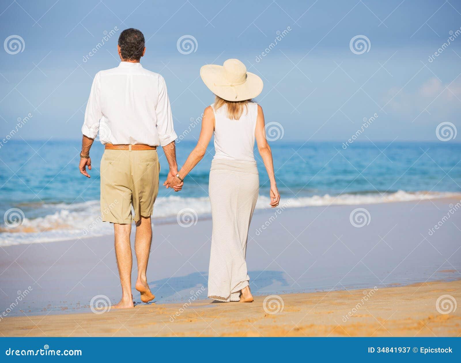 Couples supérieurs heureux sur la plage. Recherche tropicale de luxe de retraite