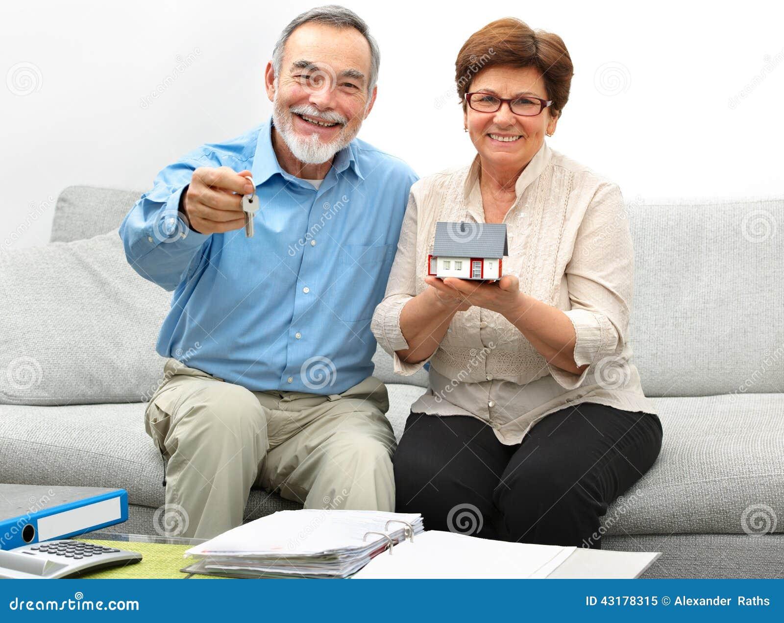 Couples supérieurs heureux tenant une petite maison