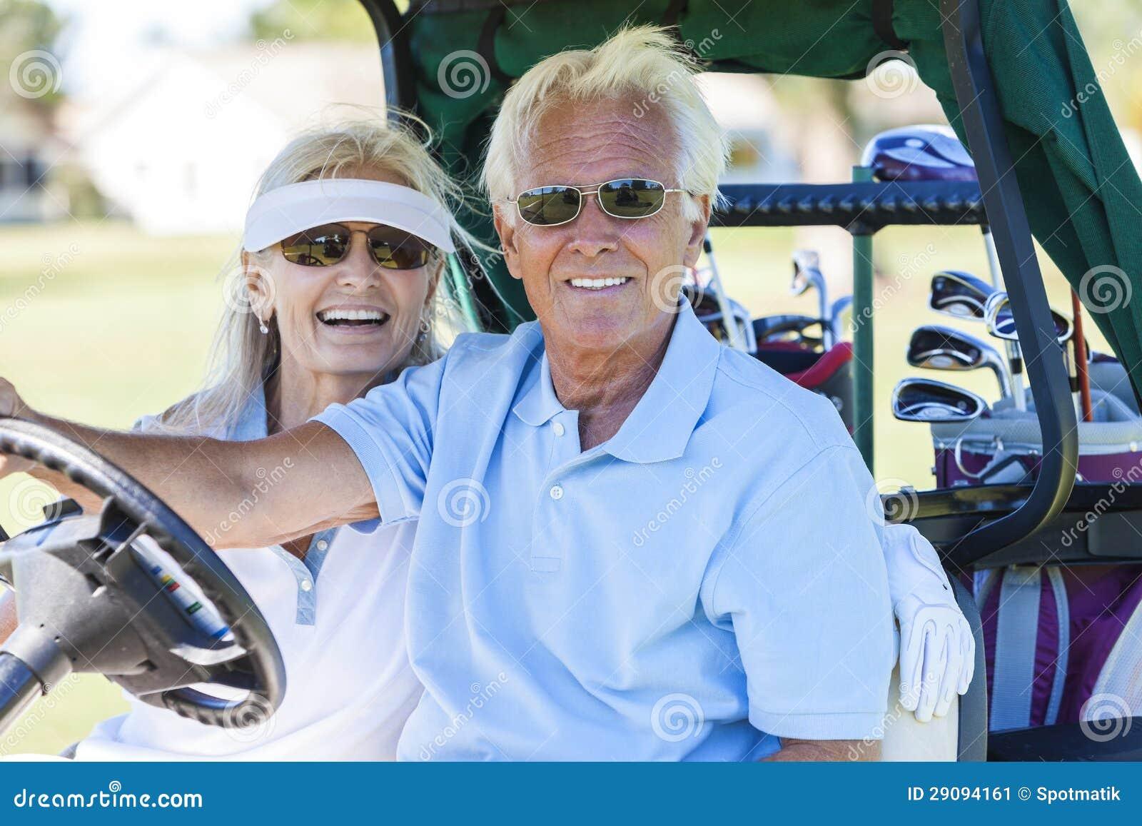 Couples supérieurs jouant au golf conduisant la poussette de chariot
