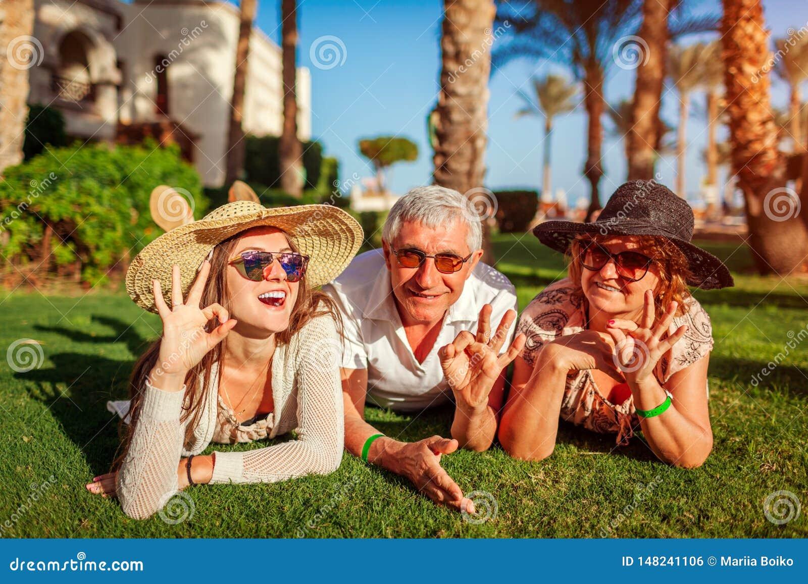 Couples supérieurs se trouvant sur l herbe avec la fille adulte par l hôtel Personnes heureuses appr?ciant des vacances Valeurs f