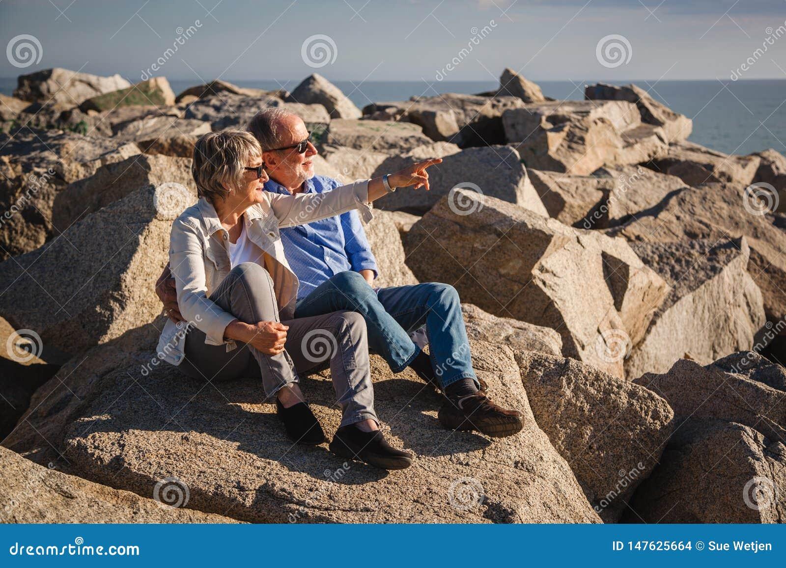 Couples sup?rieurs actifs marchant sur les roches ensoleill?es par la mer