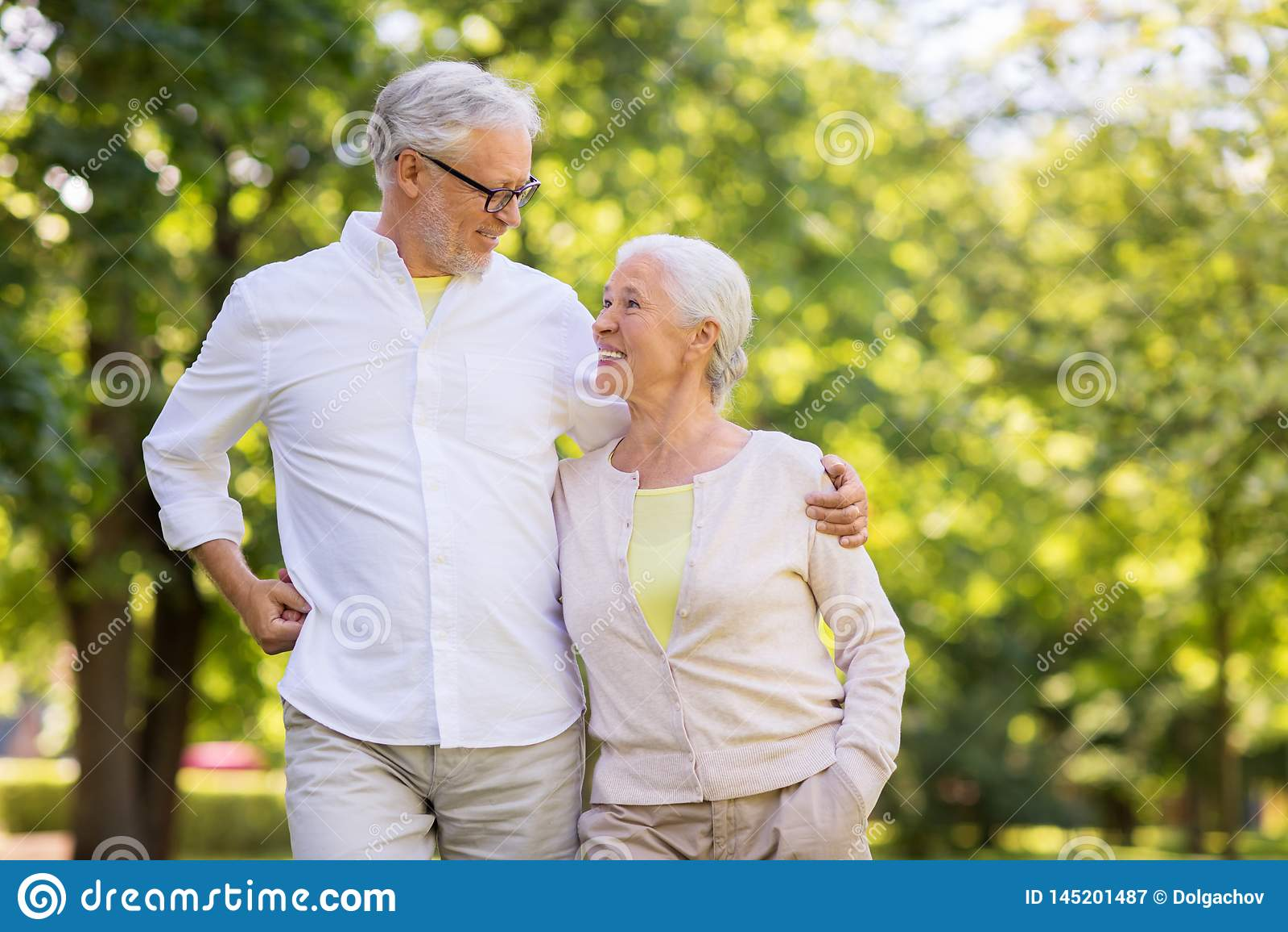 Couples sup?rieurs heureux ?treignant au parc d ?t?