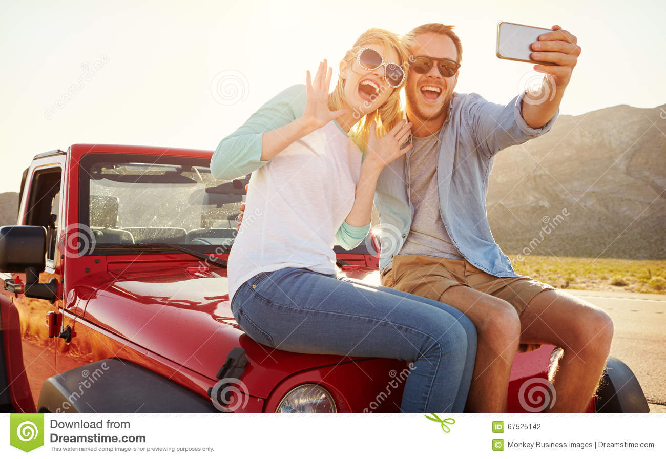 Couples sur le voyage par la route Sit On Convertible Car Taking Selfie