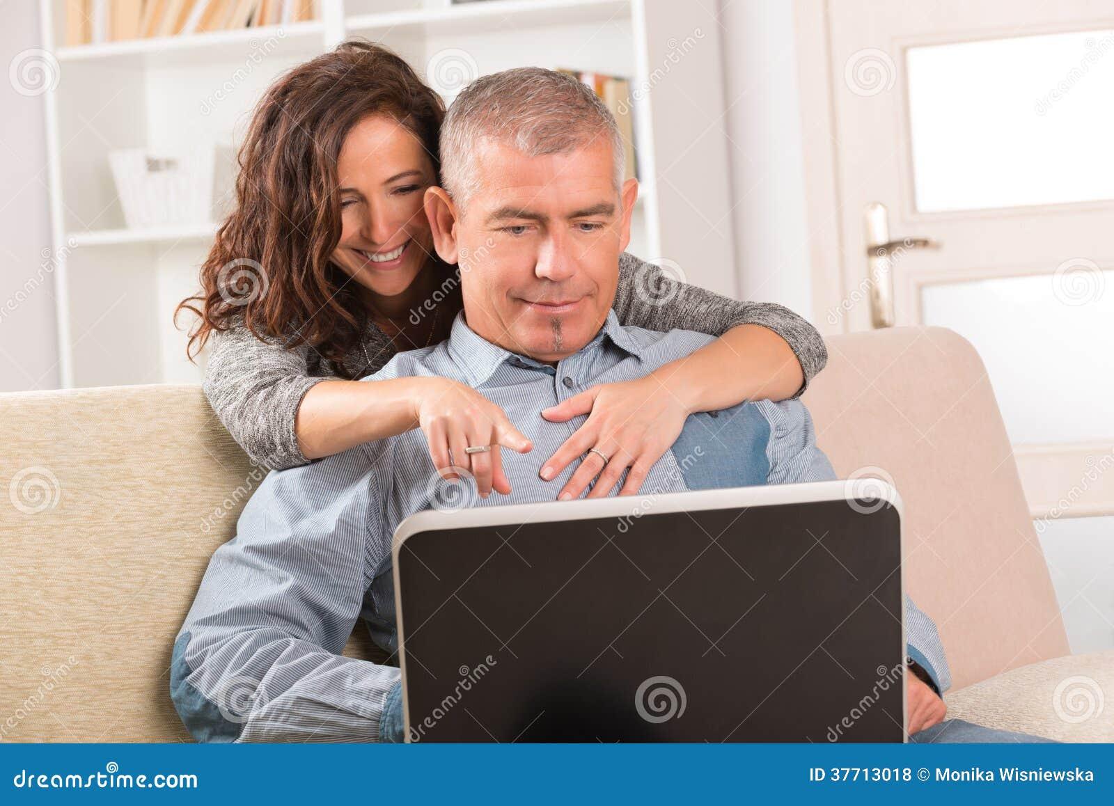 Couples utilisant l ordinateur portable à la maison