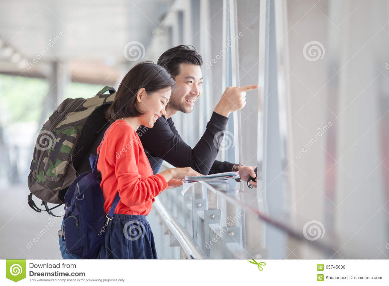 Couples of younger traveling man and woman looking to traveler g