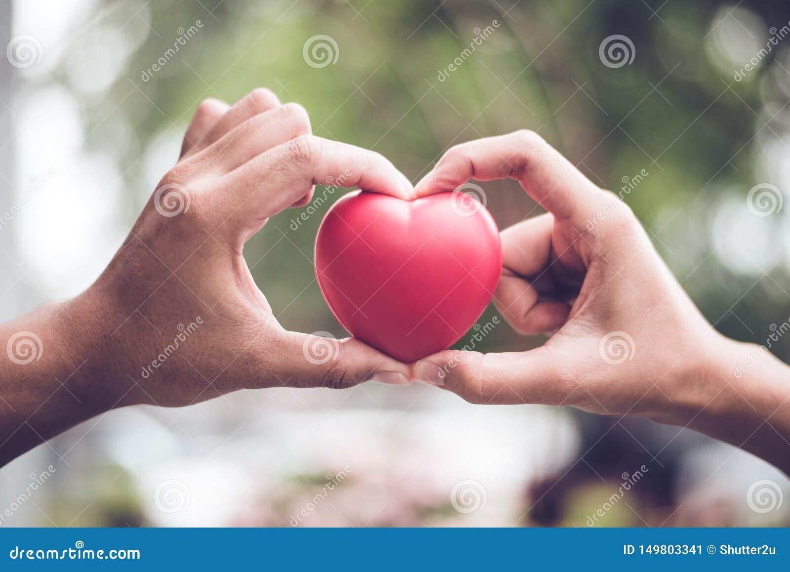 Couplez dans l amour faisant la forme de symbole de coeur avec l unit? de doigt et de mains Concept de jour de Valentines Voyage