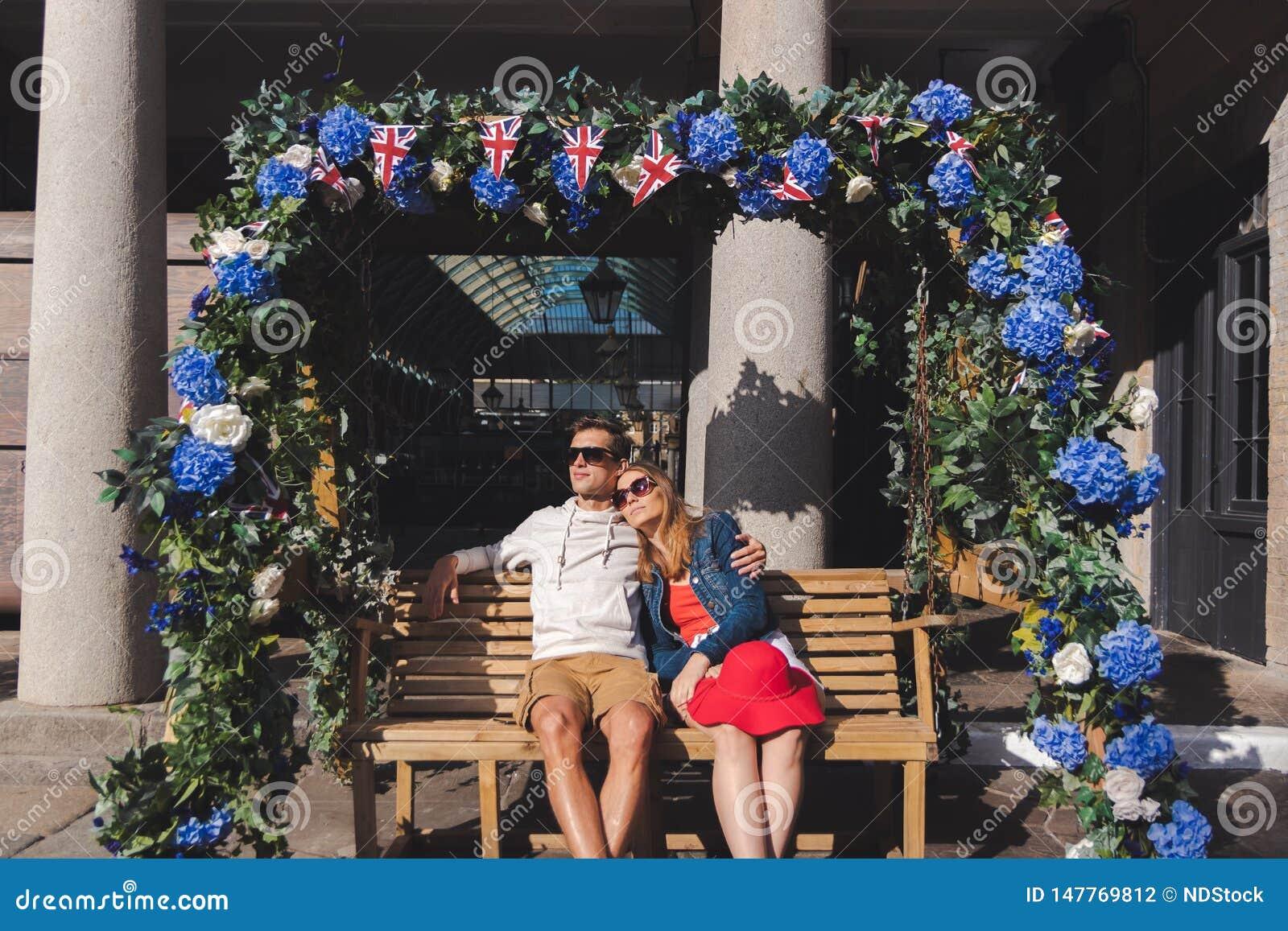 Couplez dans l amour pos? sur un banc de oscillation dans le jardin covent Londres