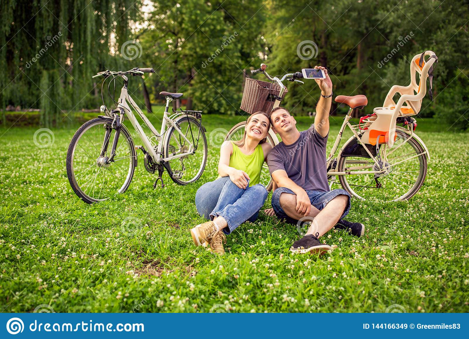 Couplez dans l amour prenant des selfies avec le smartphone en parc