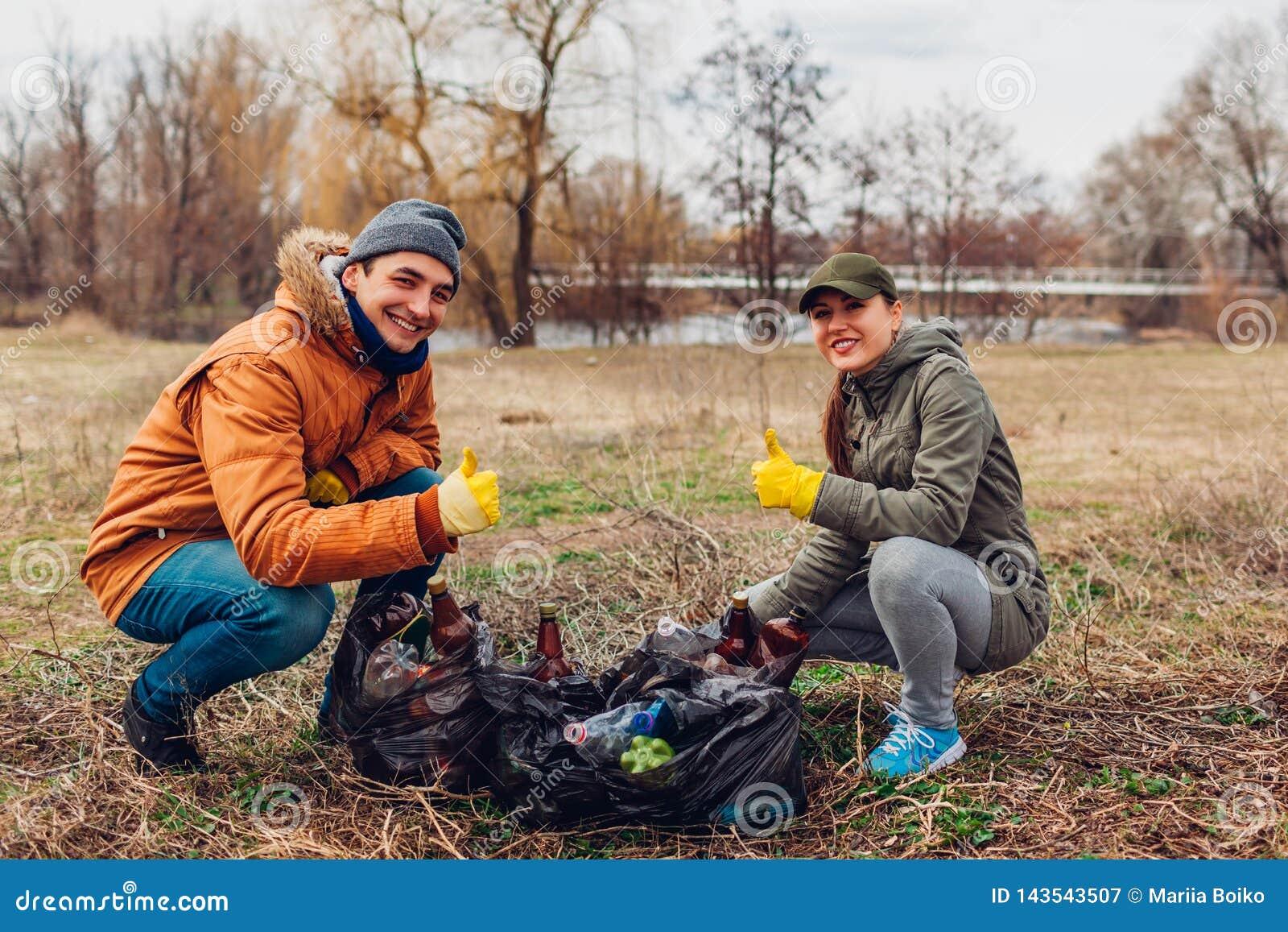 Couplez des volontaires a nettoyé les déchets en parc Les gens ont pris des déchets et résultat de représentation avec le pouce