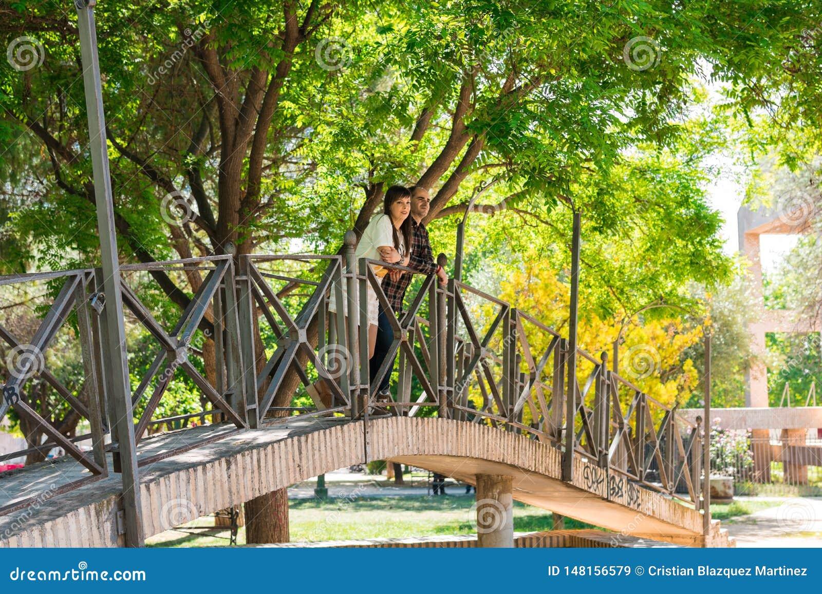Couplez en parc, ils sont sur un pont