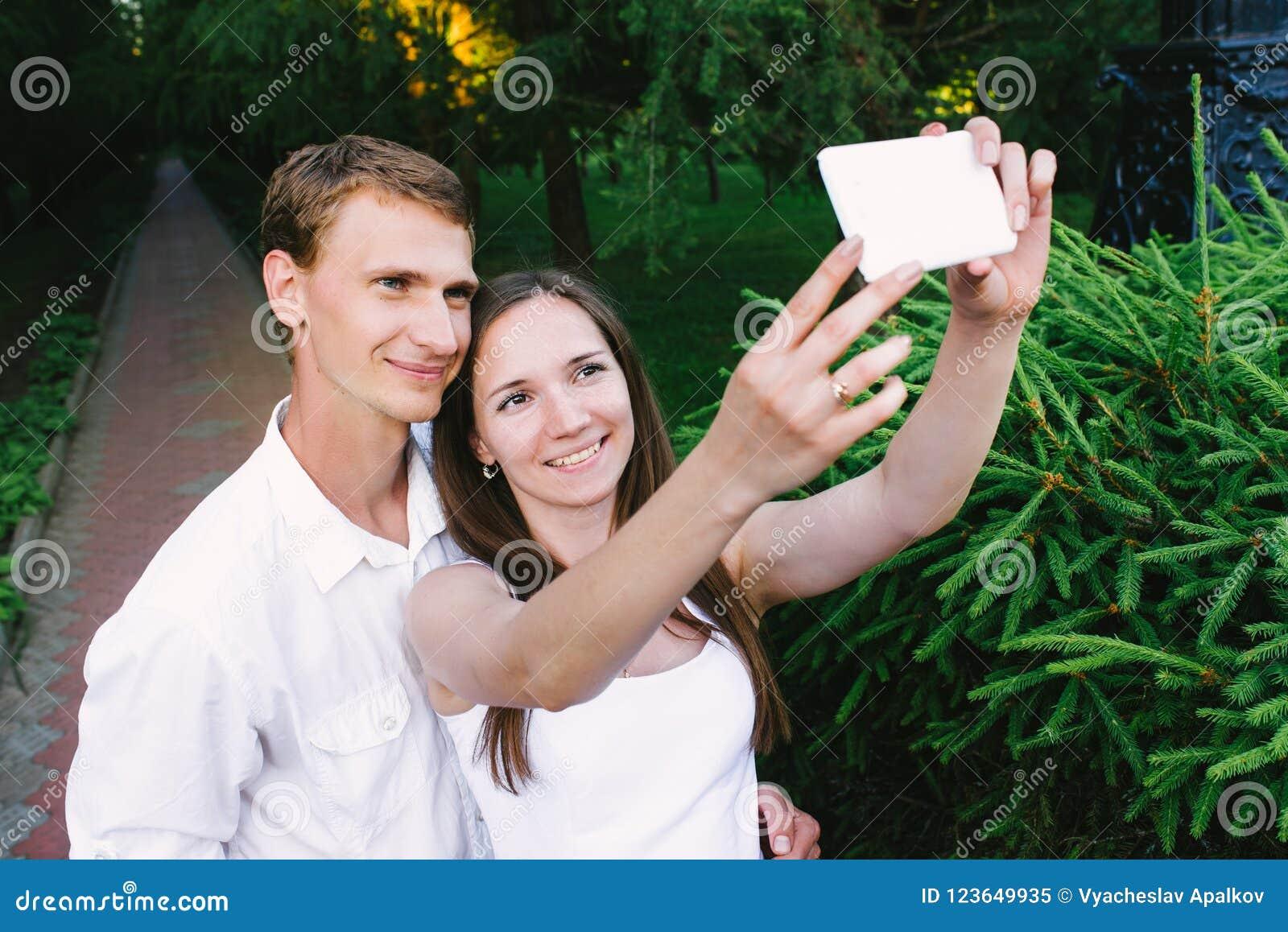 Couplez faire un selfie ensemble en parc vert