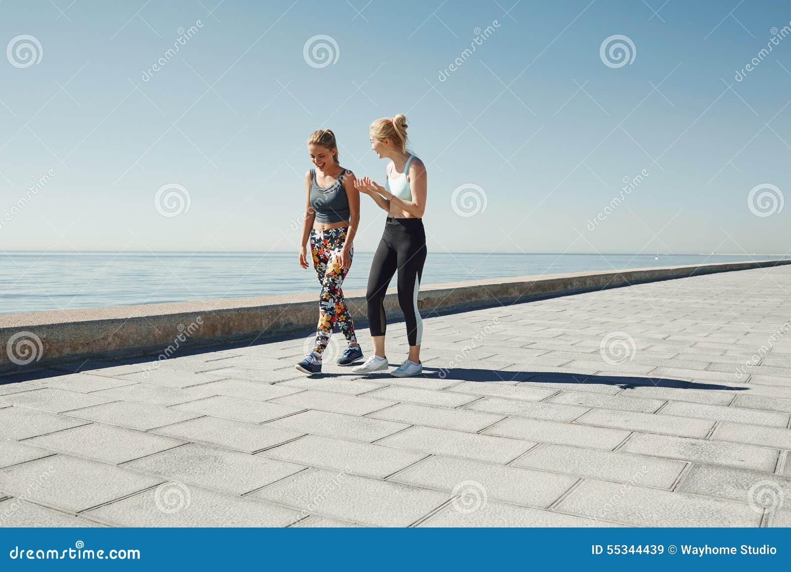 Couplez la femelle courant en exerçant pulser heureux sur le bord de mer