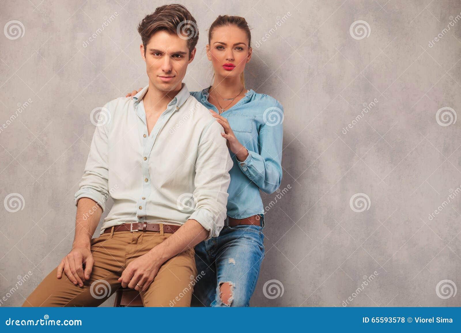 Couplez la pose, il a assis et elle dans l emb debout de fond