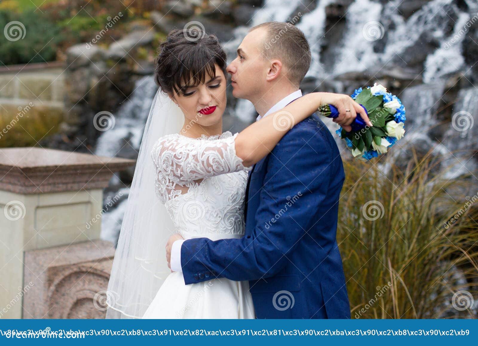 couplez la position sous la pluie le jour du mariage photo stock image 70615764. Black Bedroom Furniture Sets. Home Design Ideas