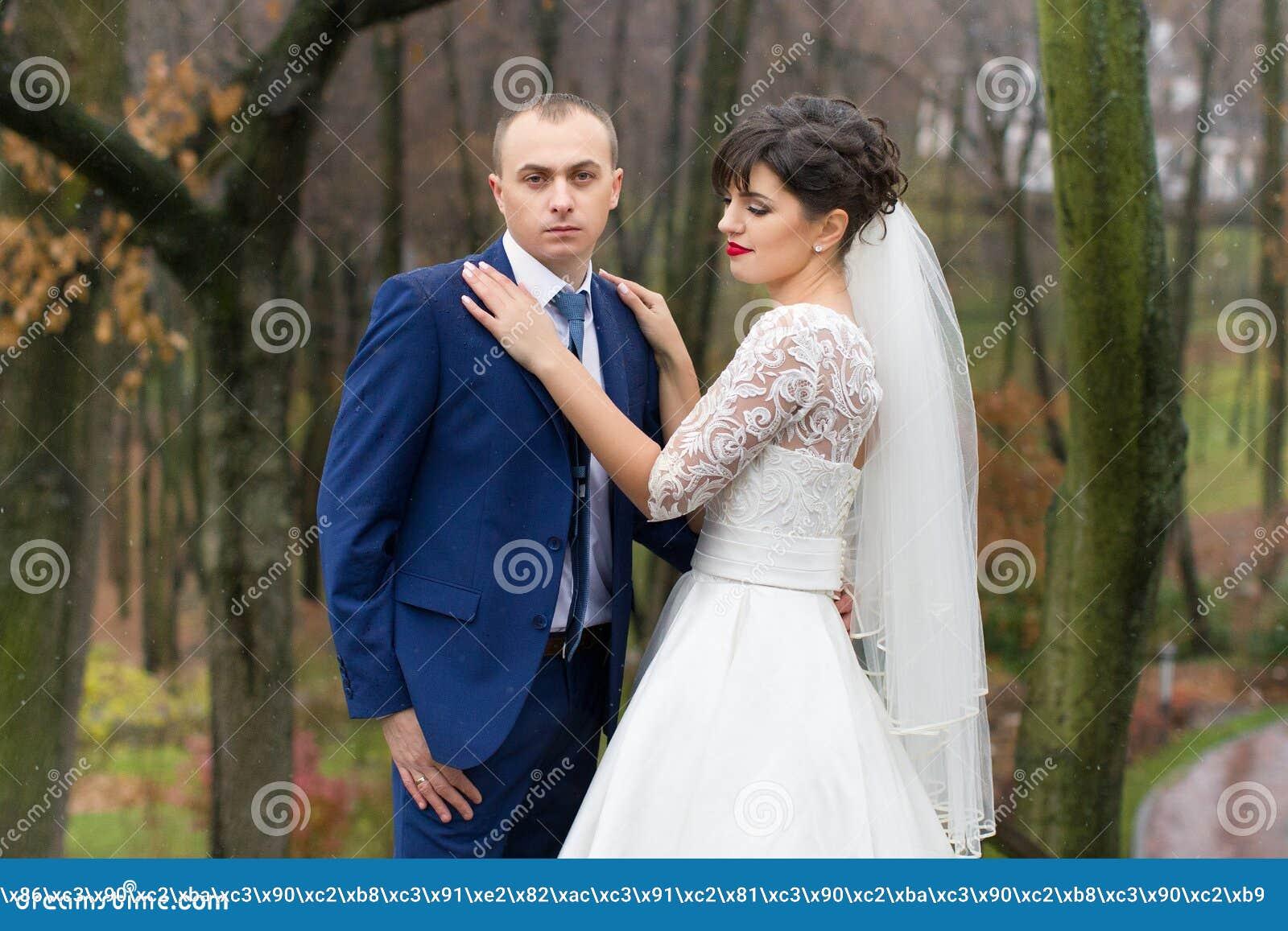 couplez la position sous la pluie le jour du mariage photo stock image 70615894. Black Bedroom Furniture Sets. Home Design Ideas