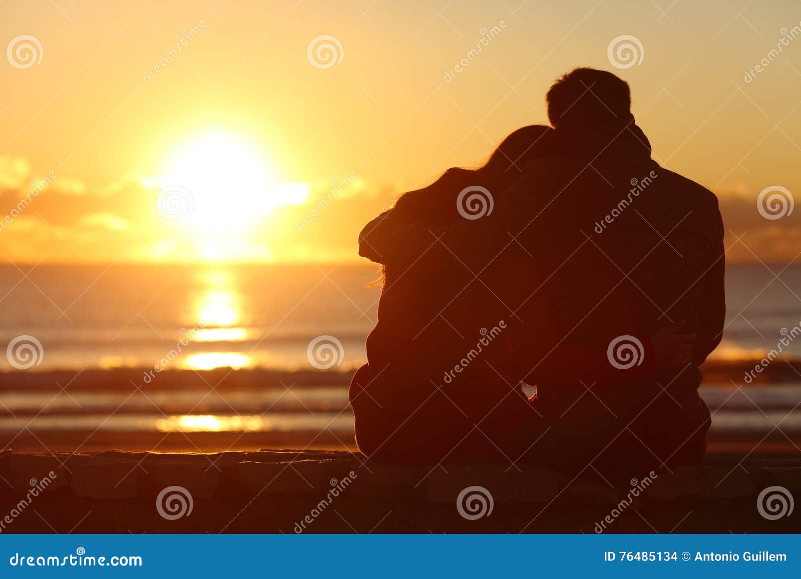 Couplez le coucher du soleil de observation sur la plage en hiver