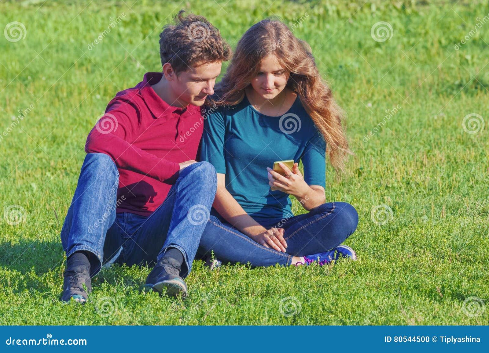 Couplez les adolescents s asseyant sur la pelouse verte avec un smartphone