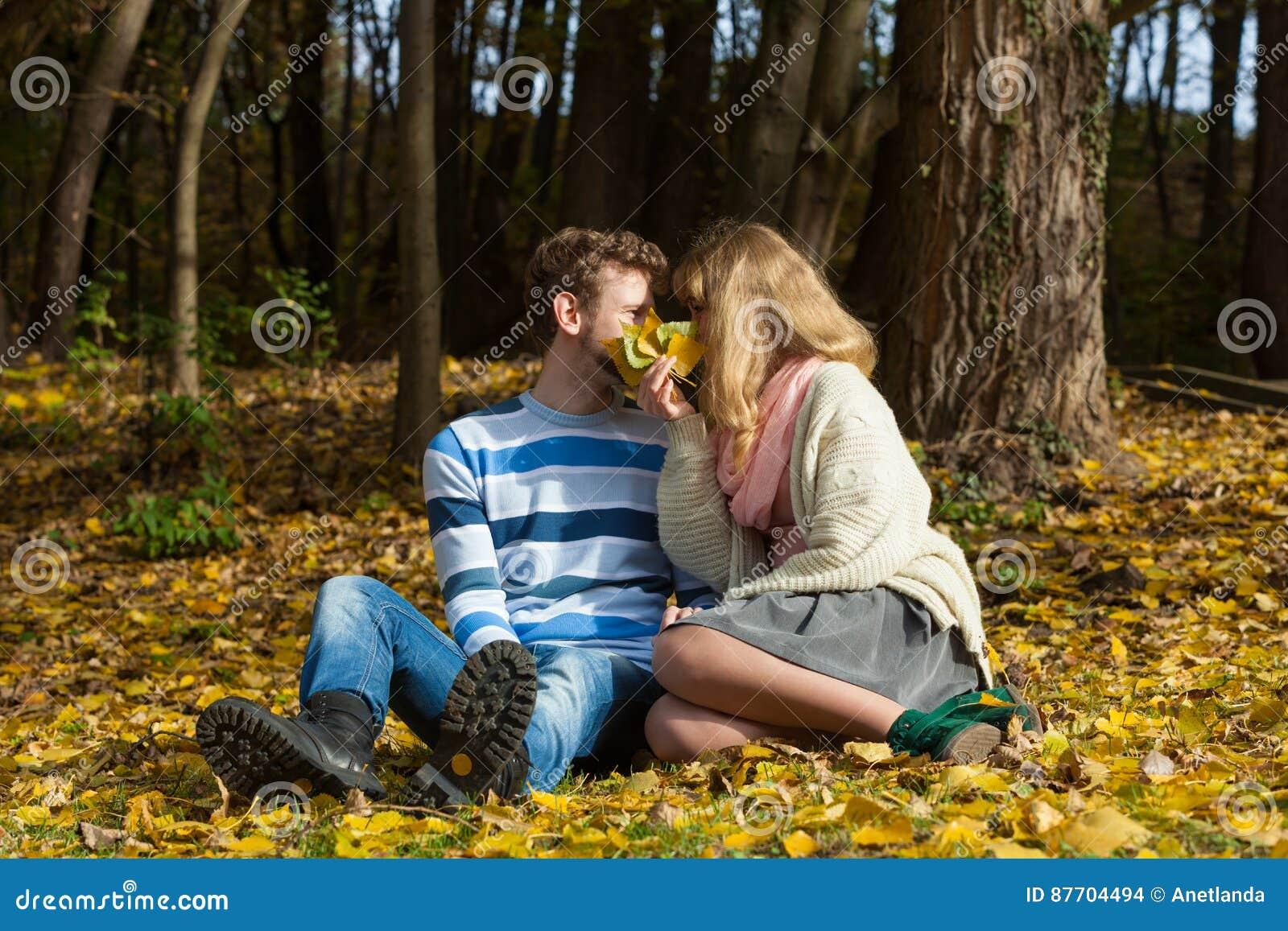 Couplez les baisers en parc d automne se cachant derrière des feuilles