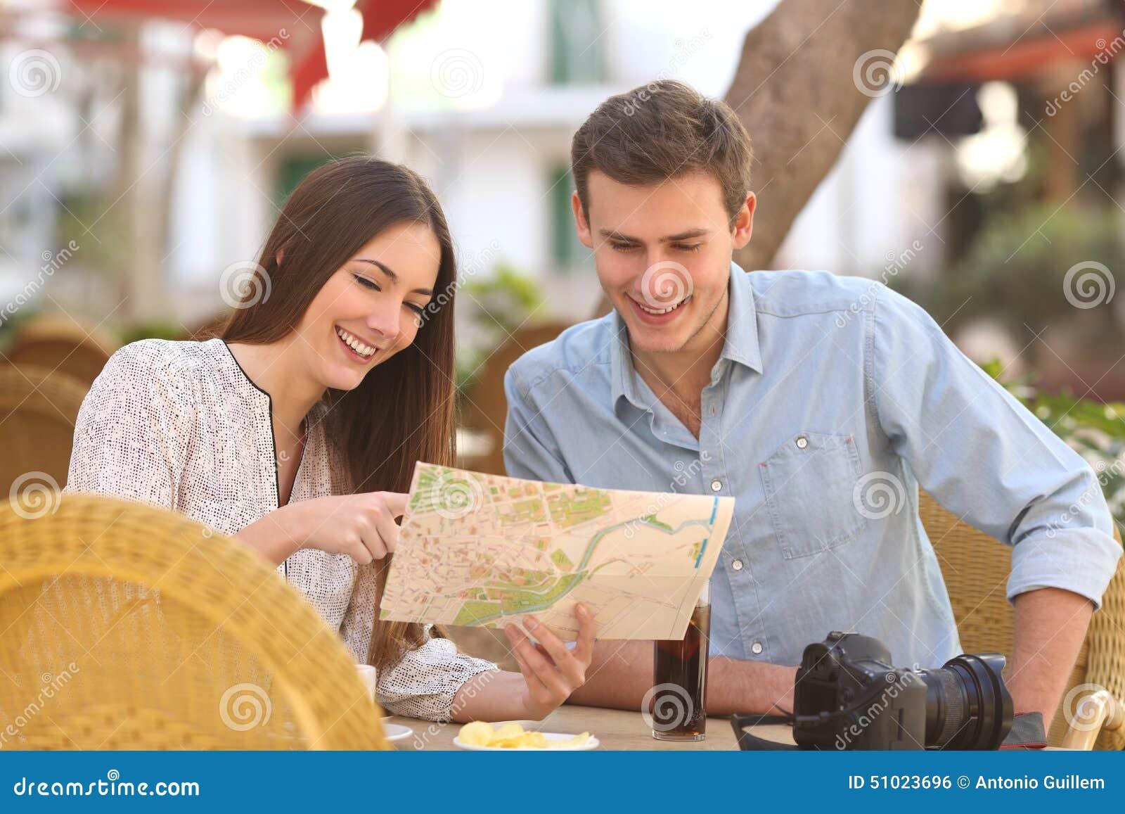 Couplez les touristes consultant un guide dans un restaurant