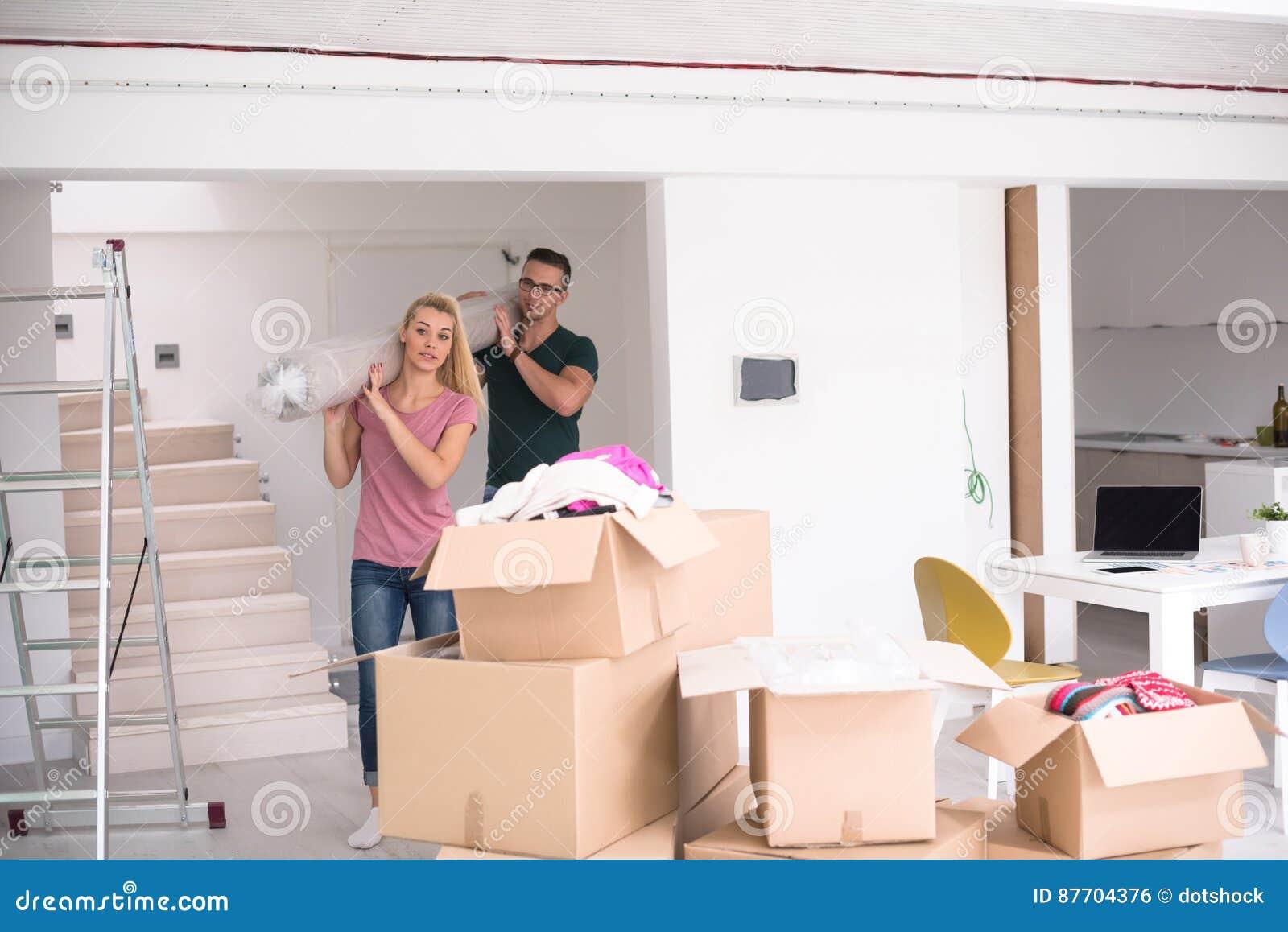 Couplez porter un tapis se déplaçant dedans à la nouvelle maison