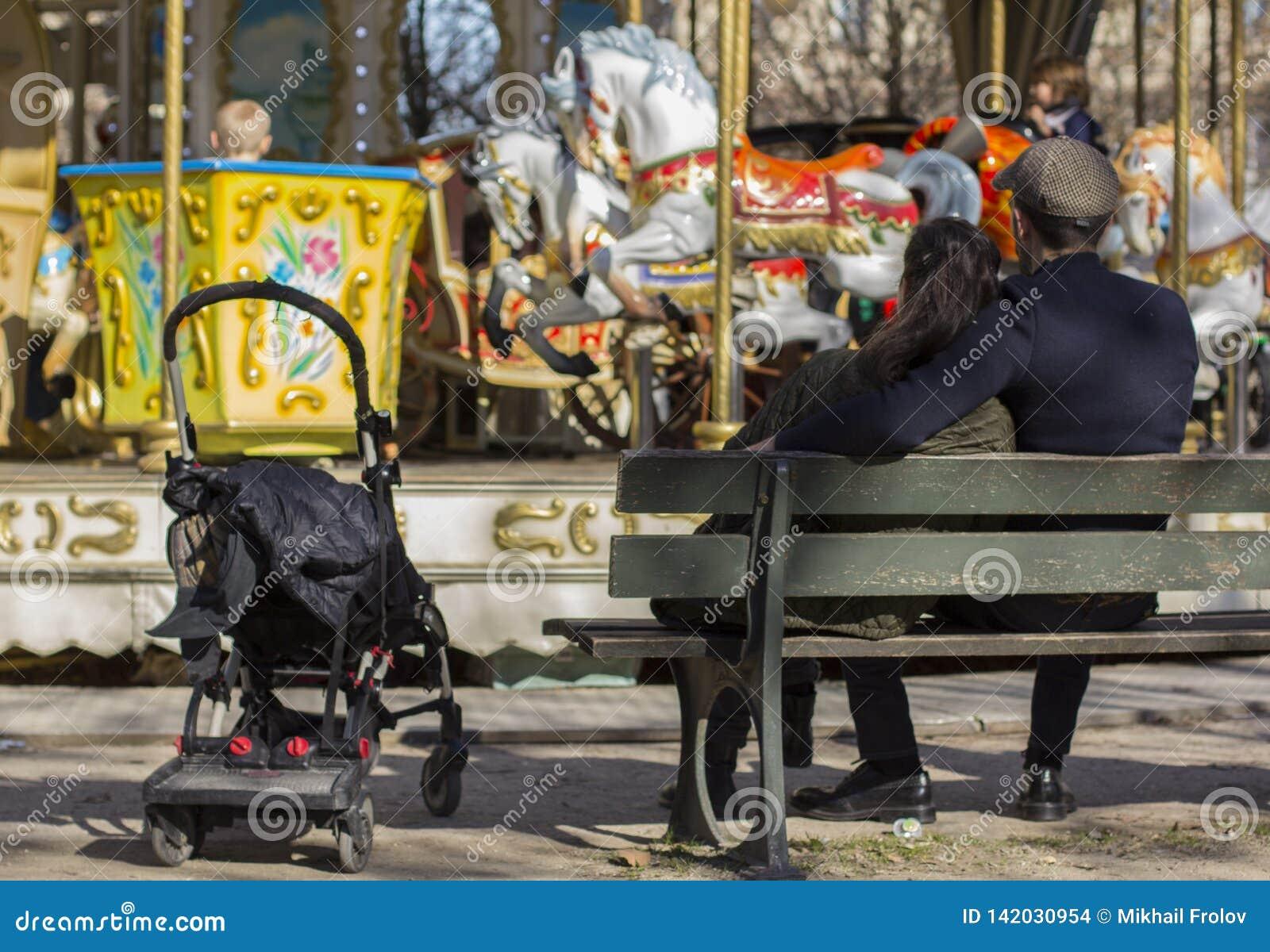 Couplez près du carrousel se reposant sur le banc attendant un carrousel de tours d enfant