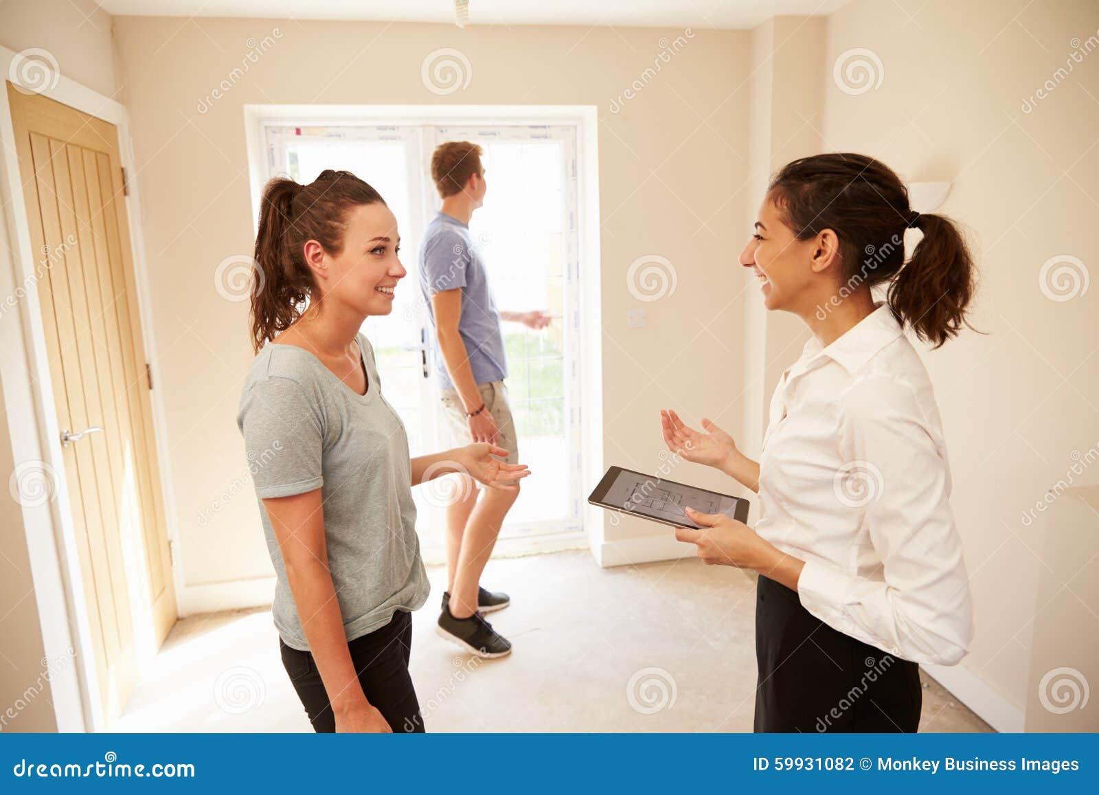 Couplez regarder un intérieur de maison avec un agent immobilier