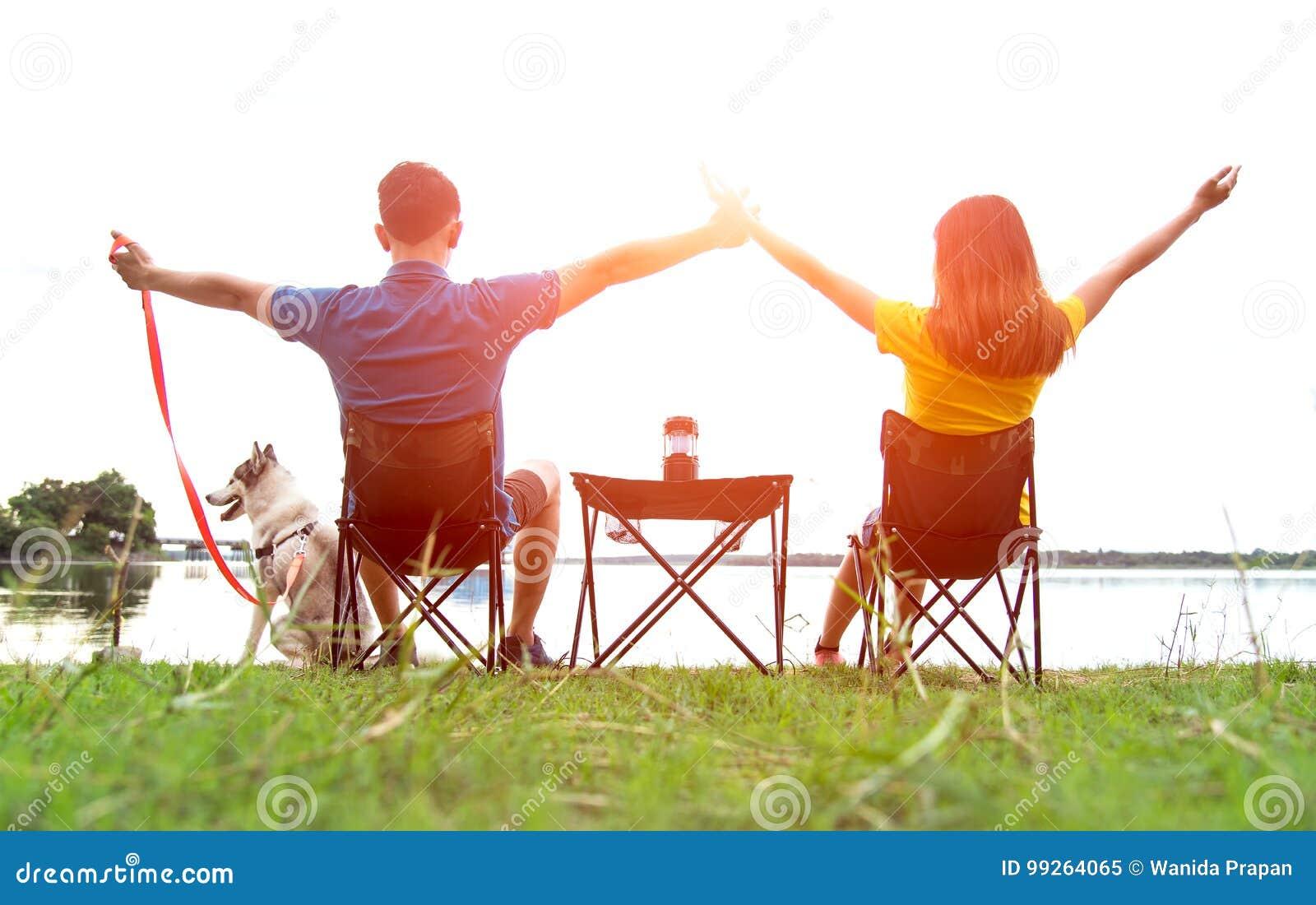 Couplez se reposer au camp brûlant avec votre chien près de la rivière sur le coucher du soleil, ainsi appréciez et jour ensoleil