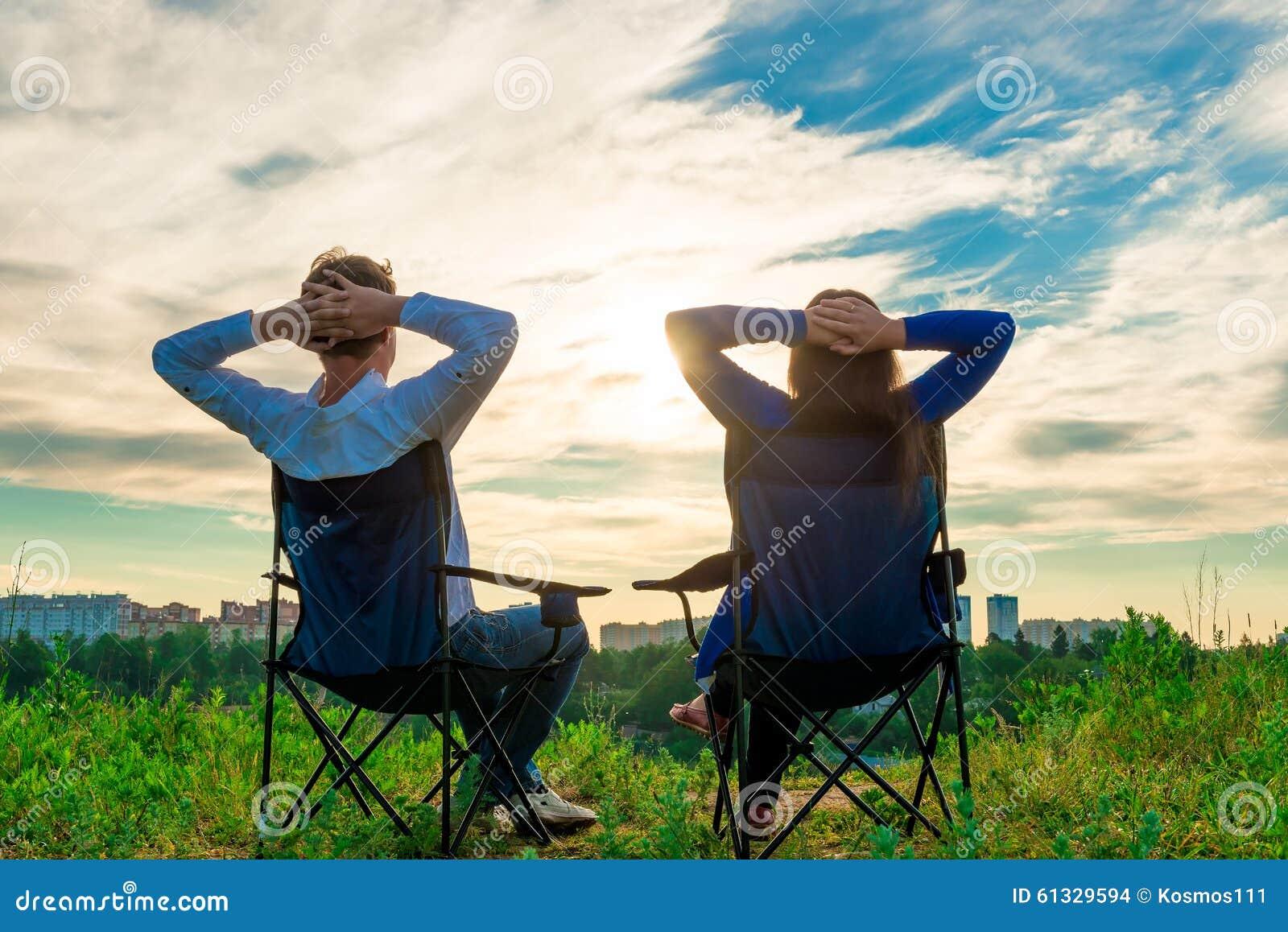 Couplez se reposer dans les chaises et admirez le lever de soleil
