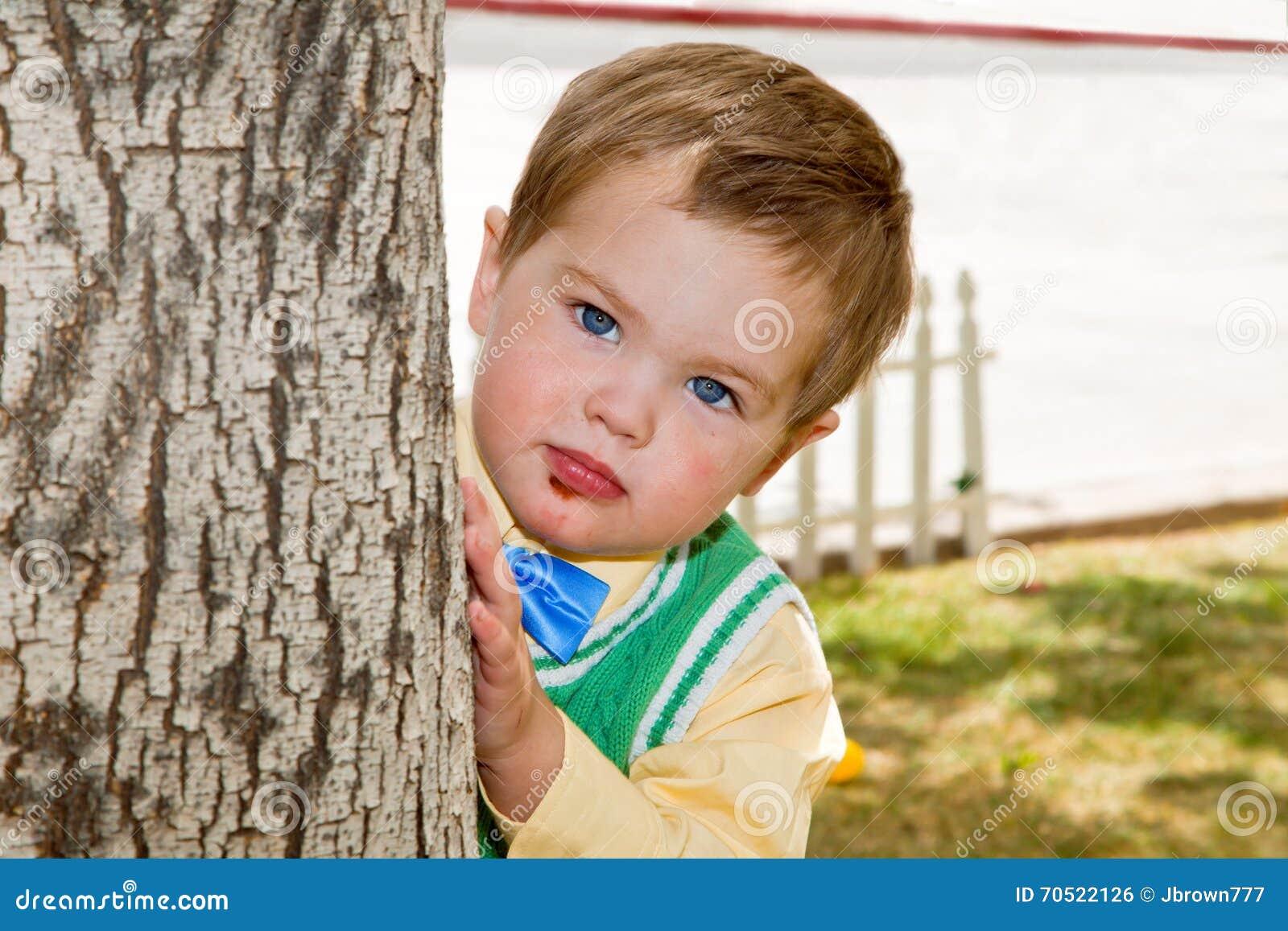Coups d oeil grincheux de garçon autour d un arbre