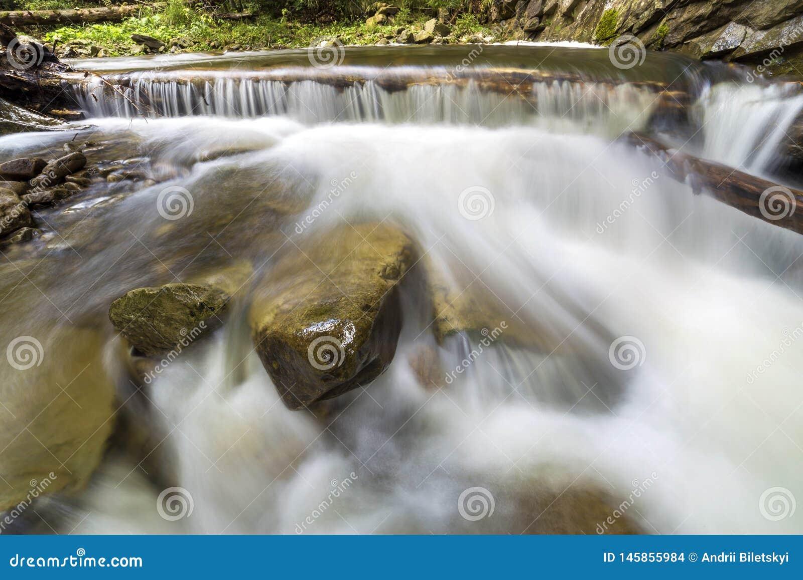 Courant fluide de rivi?re avec de l eau soyeux lisse tombant de grandes pierres en belles cascades le jour ensoleill? lumineux d