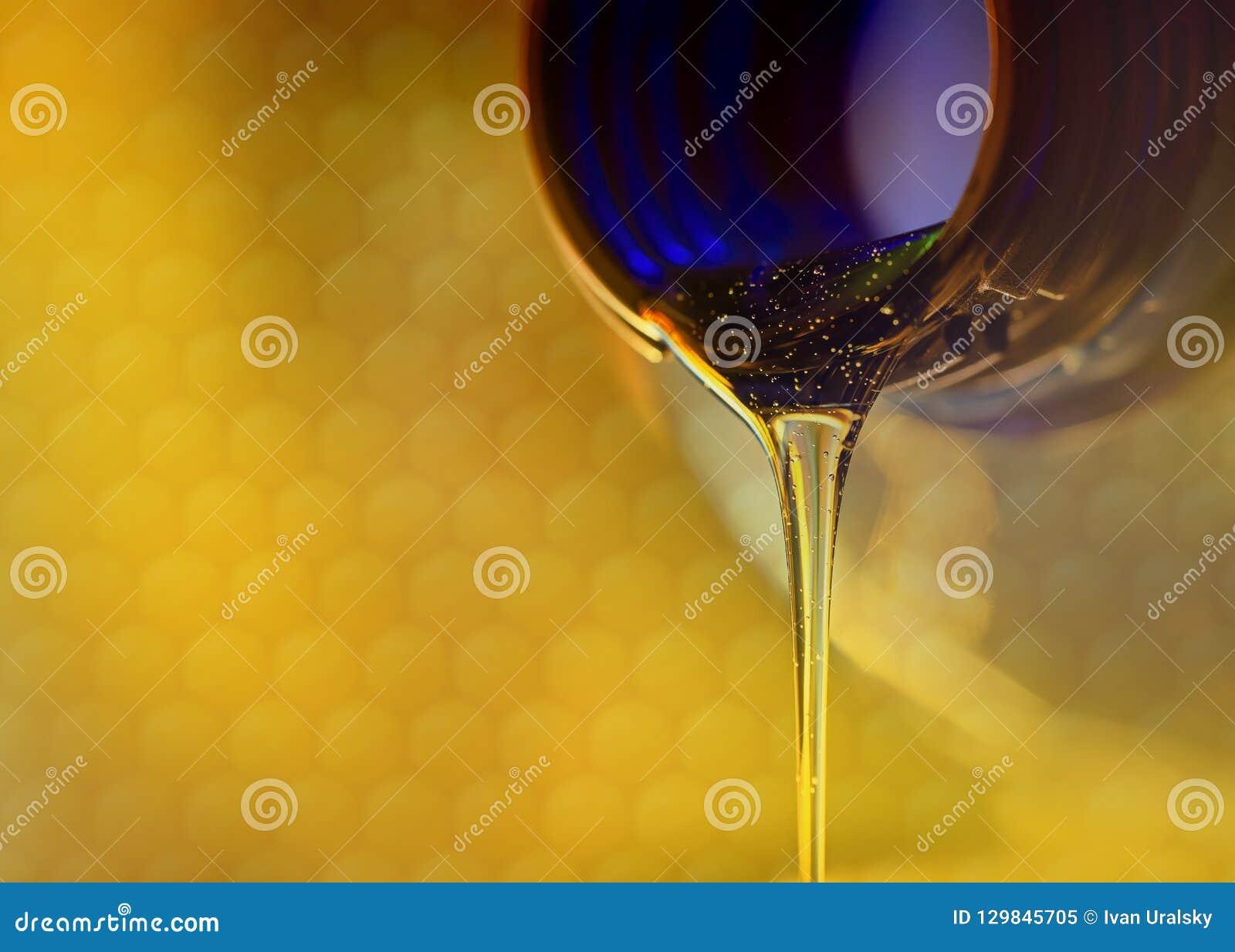 Courant liquide des écoulements doux de miel du cou du plan rapproché de bouteille