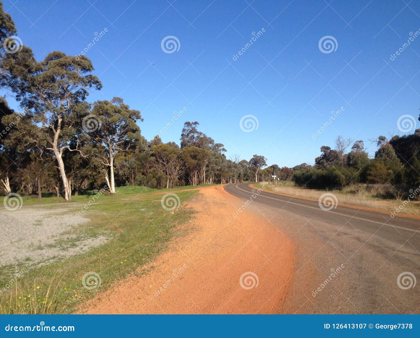 Courber la route avec les arbres, le sable et le ciel bleu dans l Australie occidentale