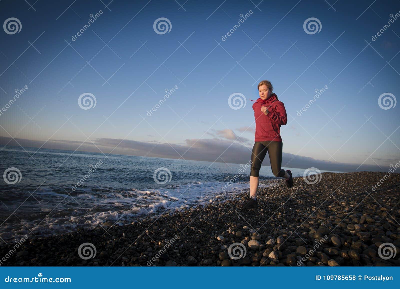 Coureur de femme adulte fonctionnant sur le bord de la mer de lever de soleil Style de vie sain