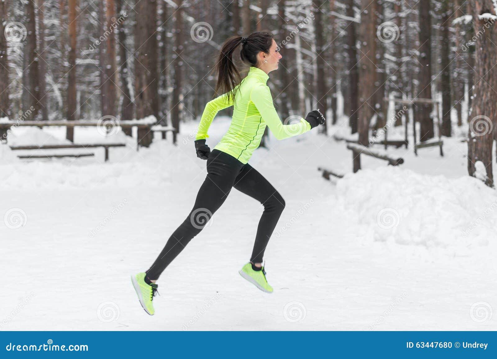 Coureur de femme d athlète fonctionnant par temps de chute de neige froid Cardio- pulser de marathon de formation de rue