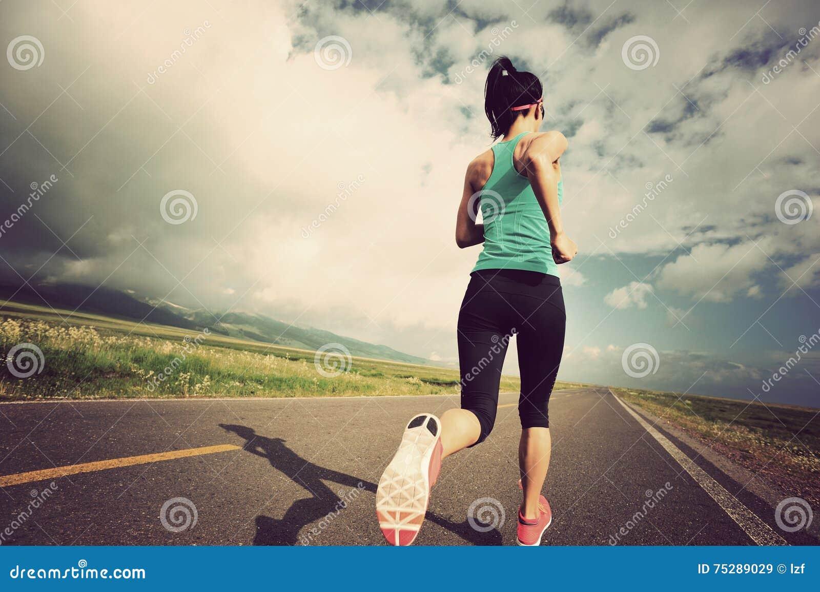 Coureur de jeune femme fonctionnant sur la belle route