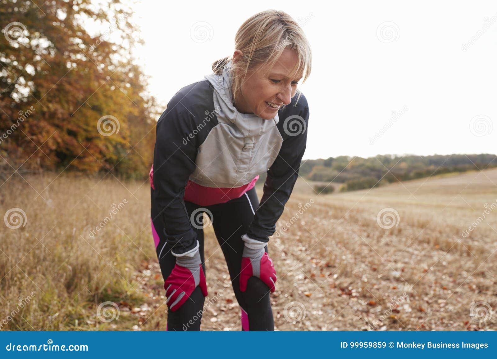 Coureur femelle mûr faisant une pause pour le souffle pendant l exercice en bois