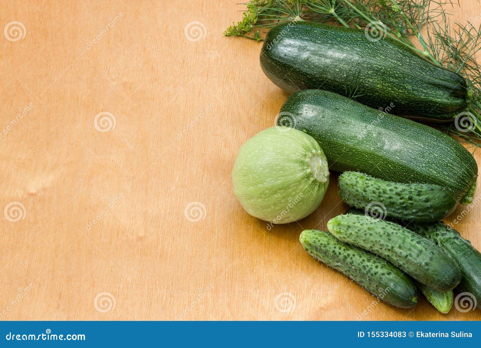Courgettes, огурцы от кроватей сада на деревянной предпосылке Овощи страны