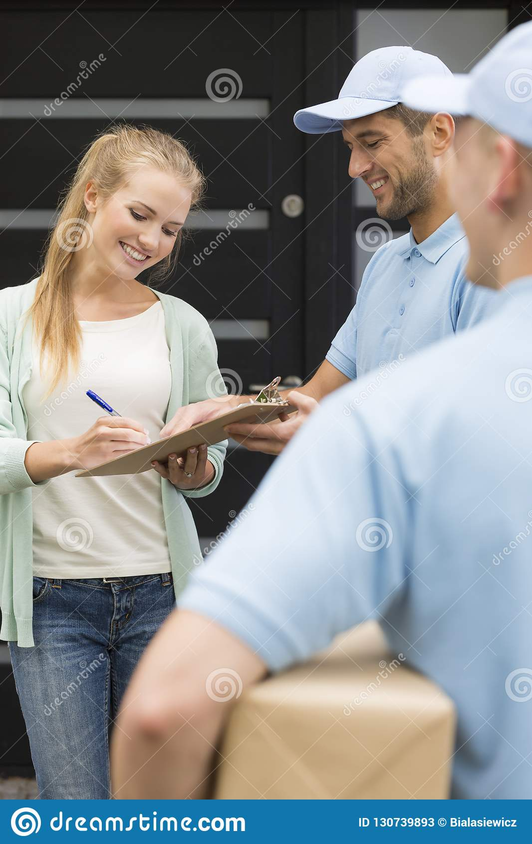 Couriers and smiling customer signing receipt of package delivery